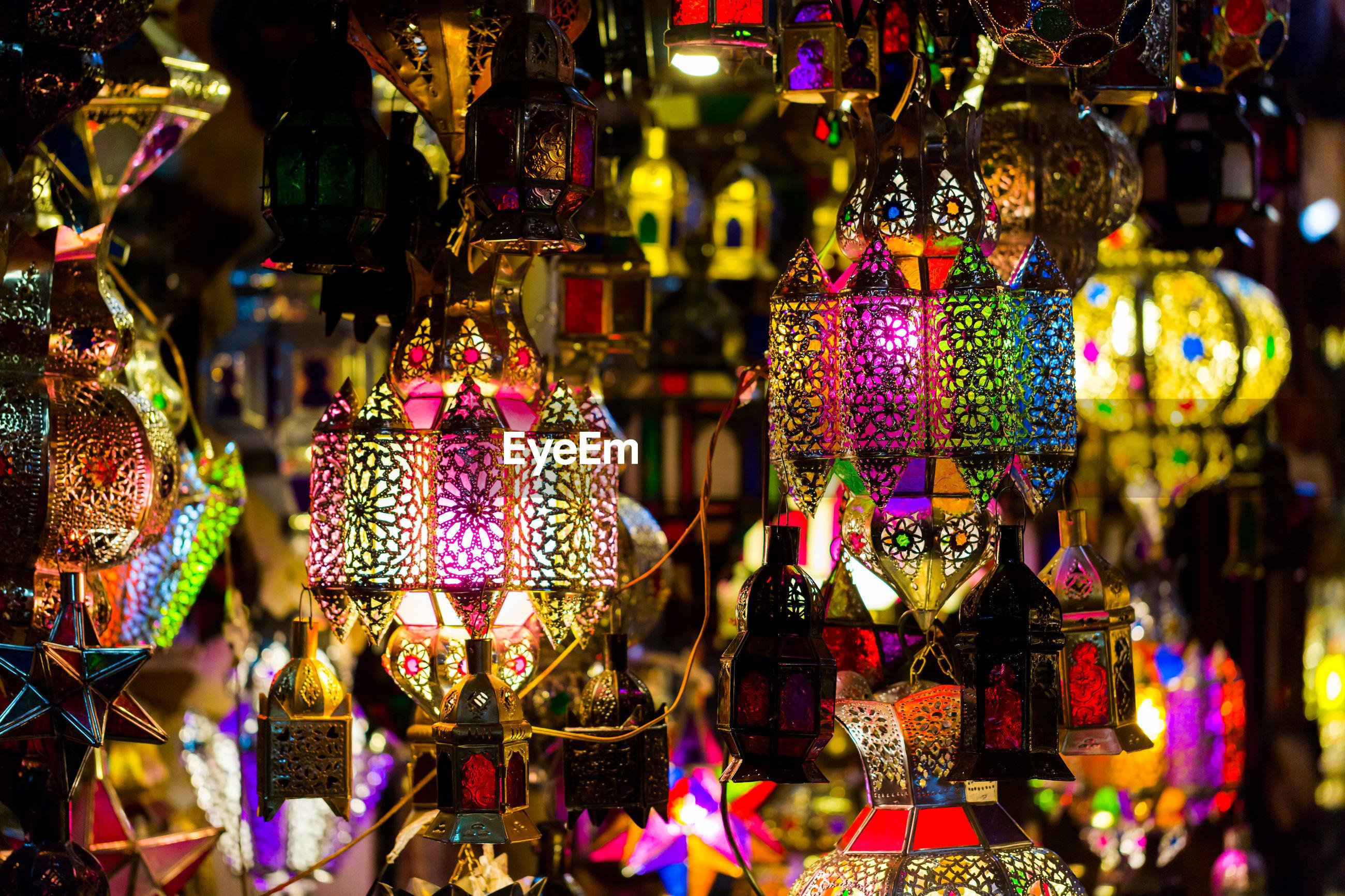 Illuminated lanterns hanging at market for sale during night