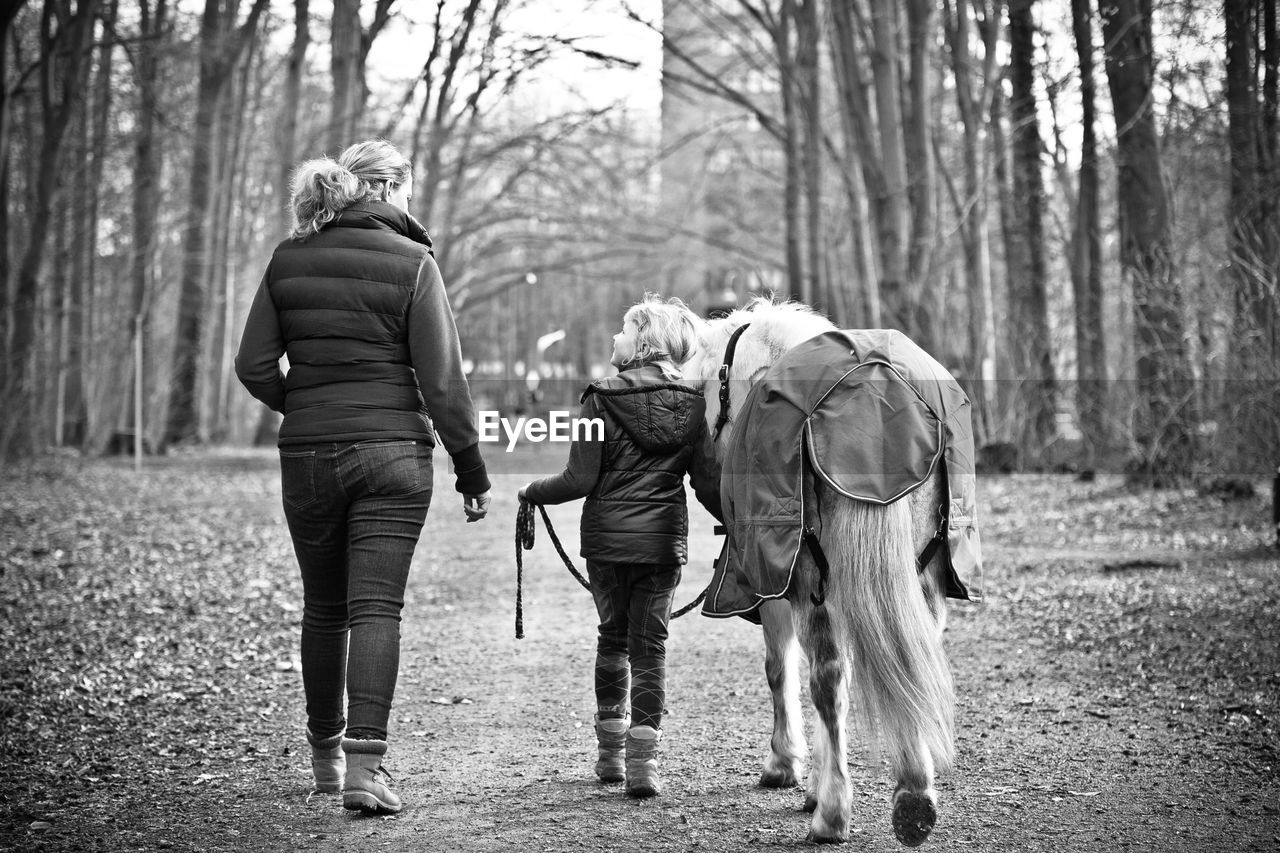 Rear view of mother and daughter with horse walking at park