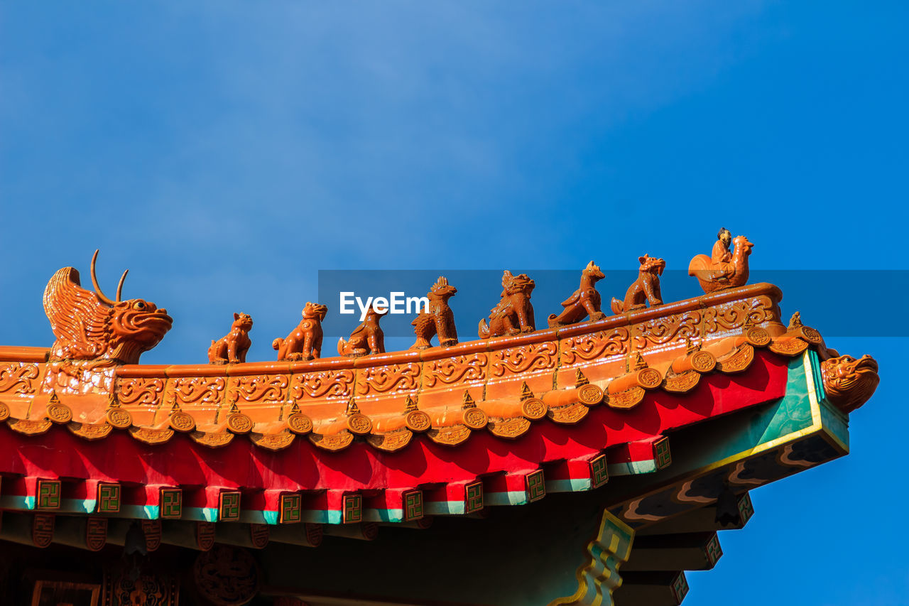 Cropped image of shrine against blue sky