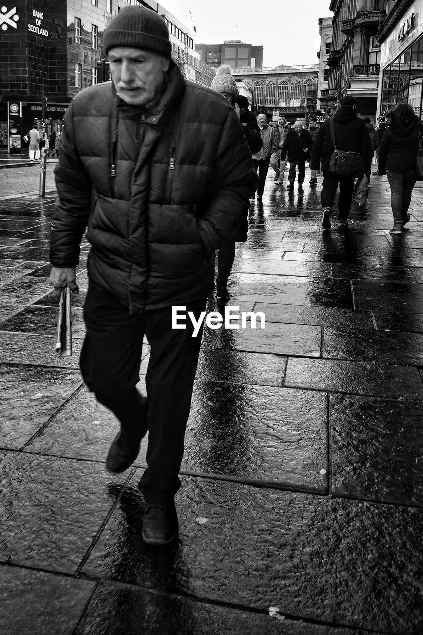 PORTRAIT OF MAN STANDING ON WET STREET
