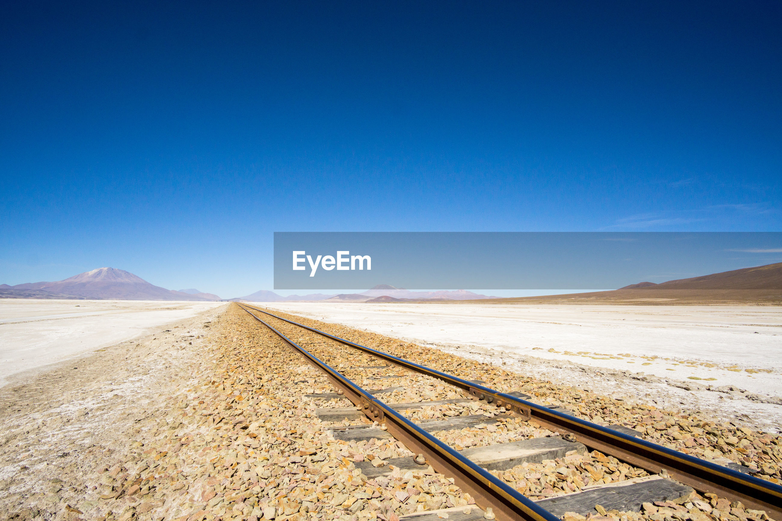 Scenic view of train tracks in desert against clear blue sky