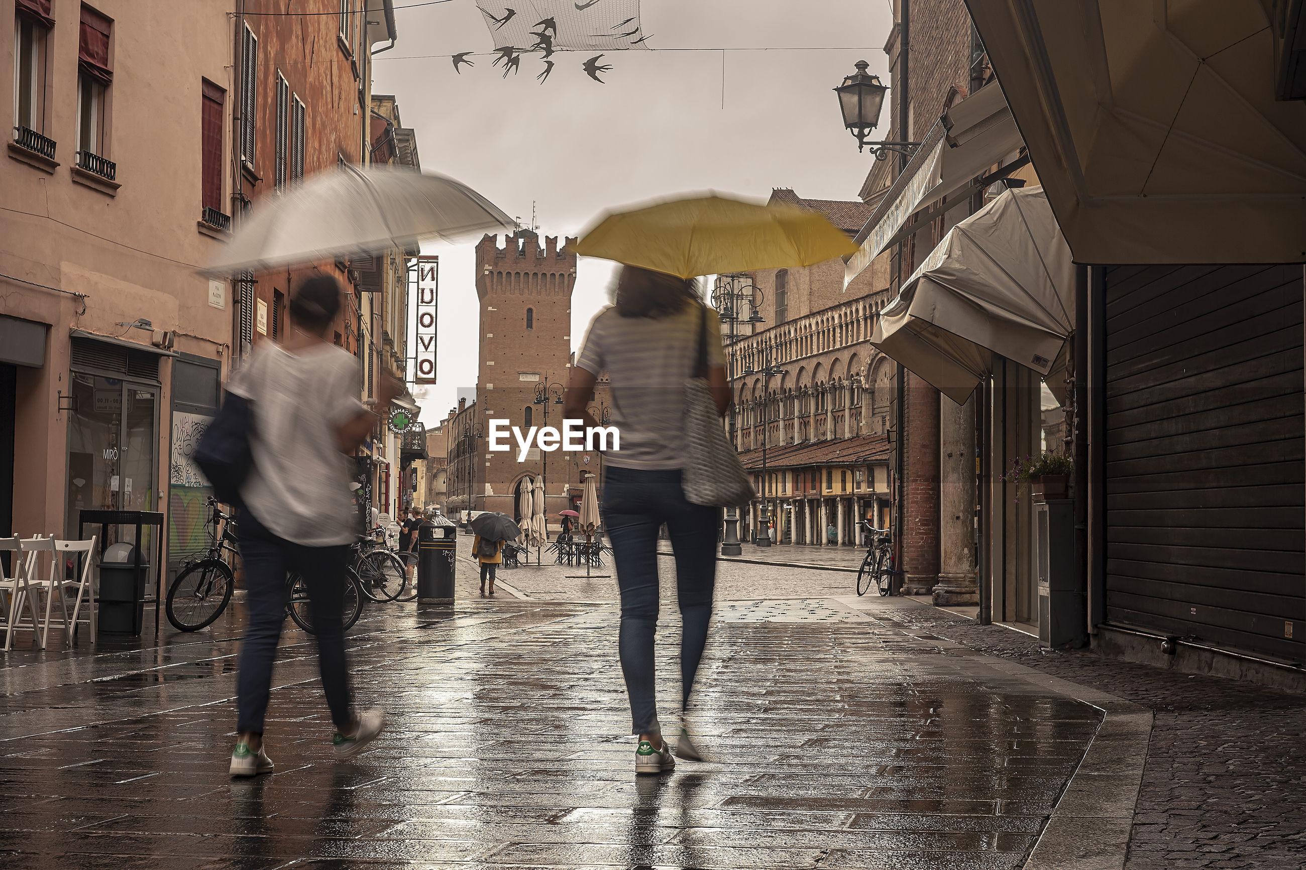 REAR VIEW OF PEOPLE WALKING ON WET STREET IN RAINY SEASON
