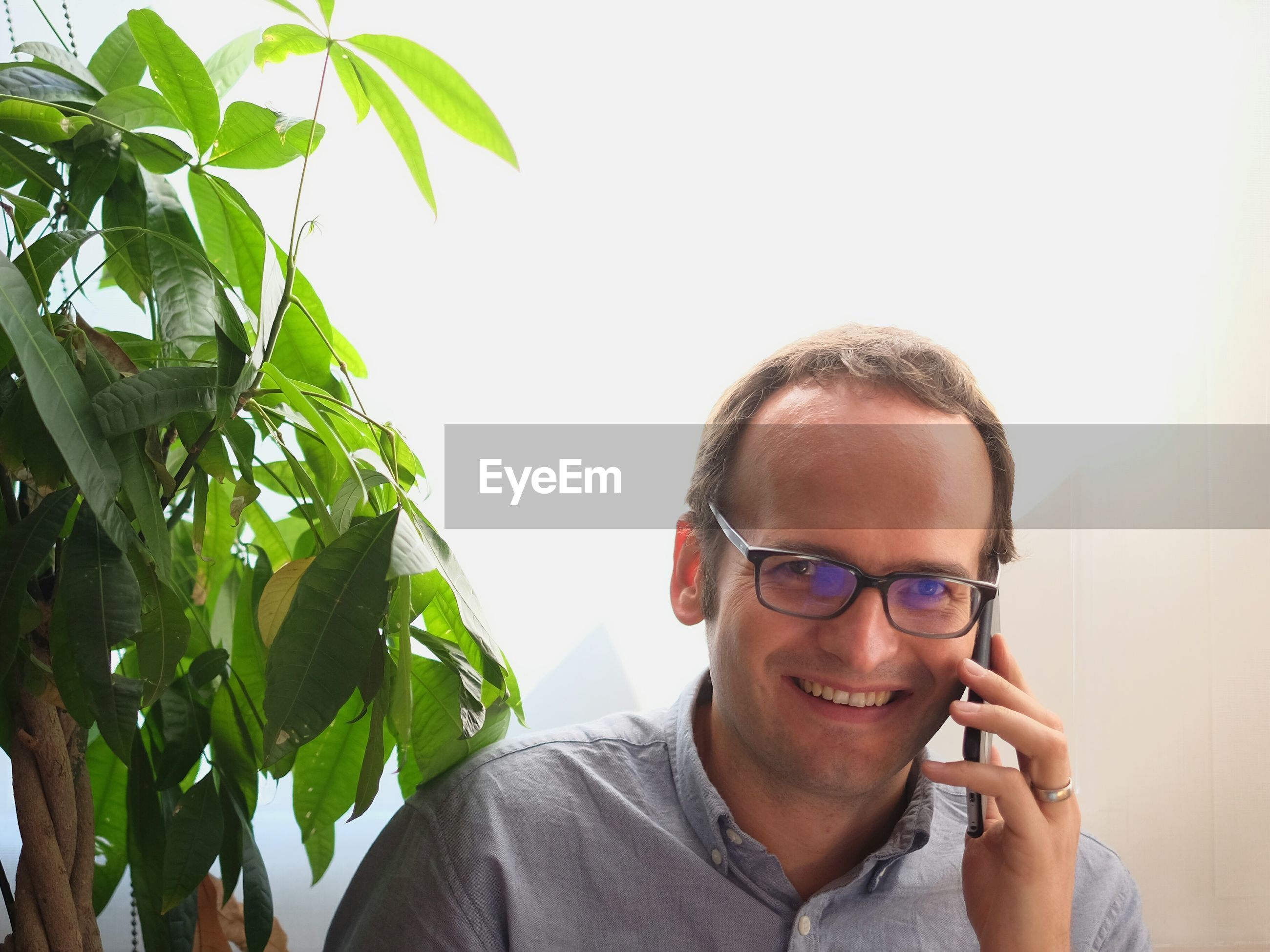 Portrait of happy man listening to mobile phone by plant against wall