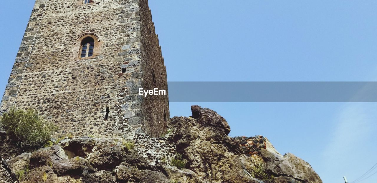 sky, built structure, architecture, low angle view, clear sky, day, building exterior, nature, building, no people, copy space, history, the past, blue, old, rock, solid, outdoors, mountain, arch, stone wall