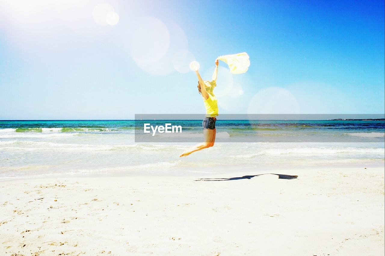 sea, beach, one person, horizon over water, sand, water, full length, leisure activity, nature, real people, motion, mid-air, sunlight, day, beauty in nature, jumping, lifestyles, outdoors, skill, sky, vacations, scenics, energetic, young adult, adult, people