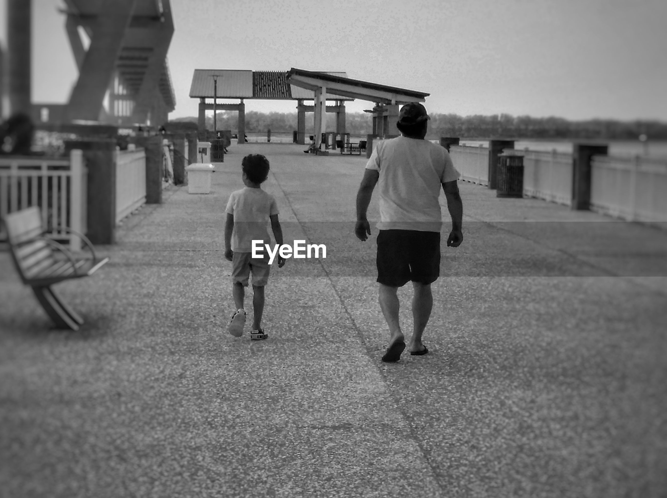 Rear view of father and son walking on footpath