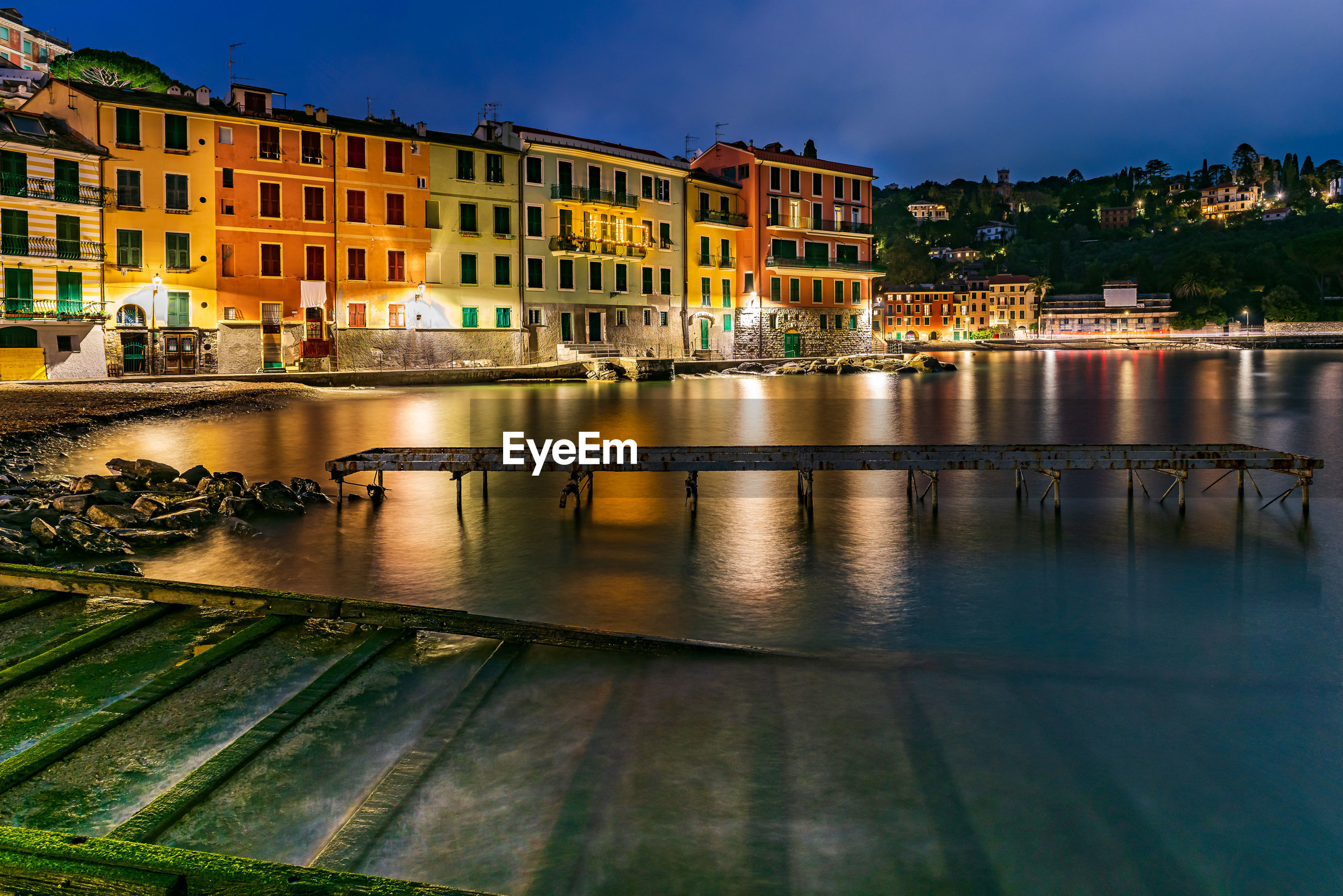 Rusty pier on lake against buildings in illuminated city at night