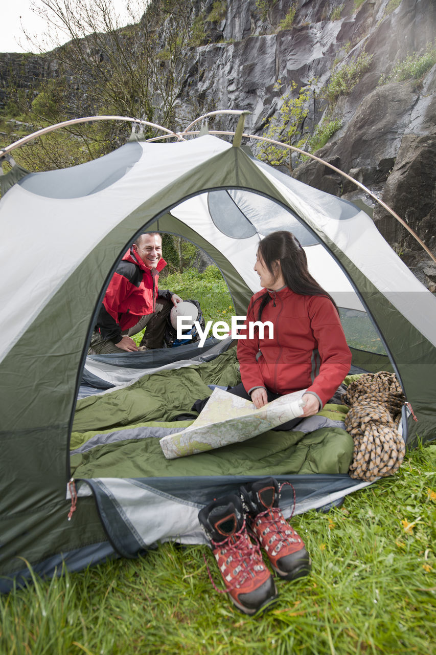 HIGH ANGLE VIEW OF FRIENDS SITTING AT TENT