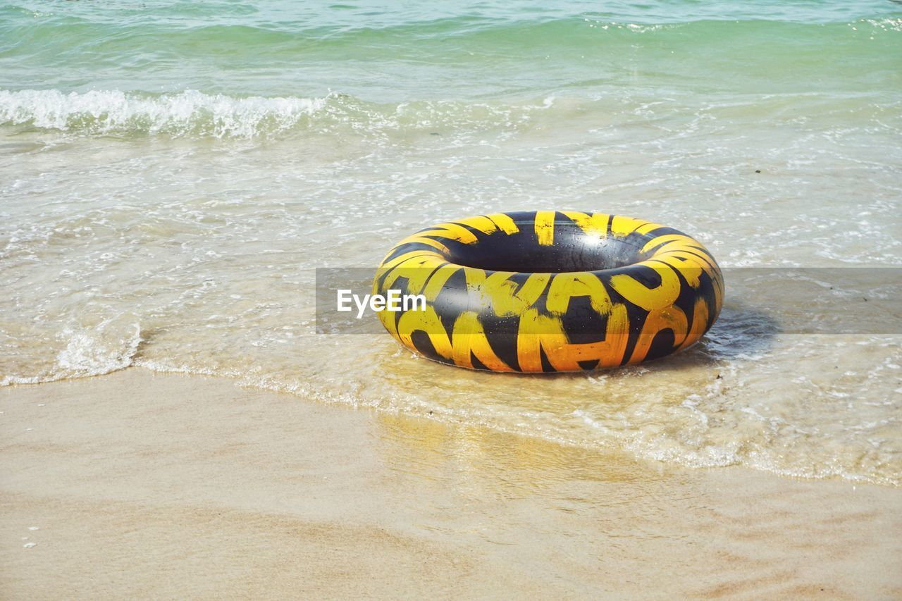 sea, water, beach, land, yellow, no people, wave, sport, beauty in nature, day, nature, motion, sand, aquatic sport, outdoors, close-up, high angle view, sunlight