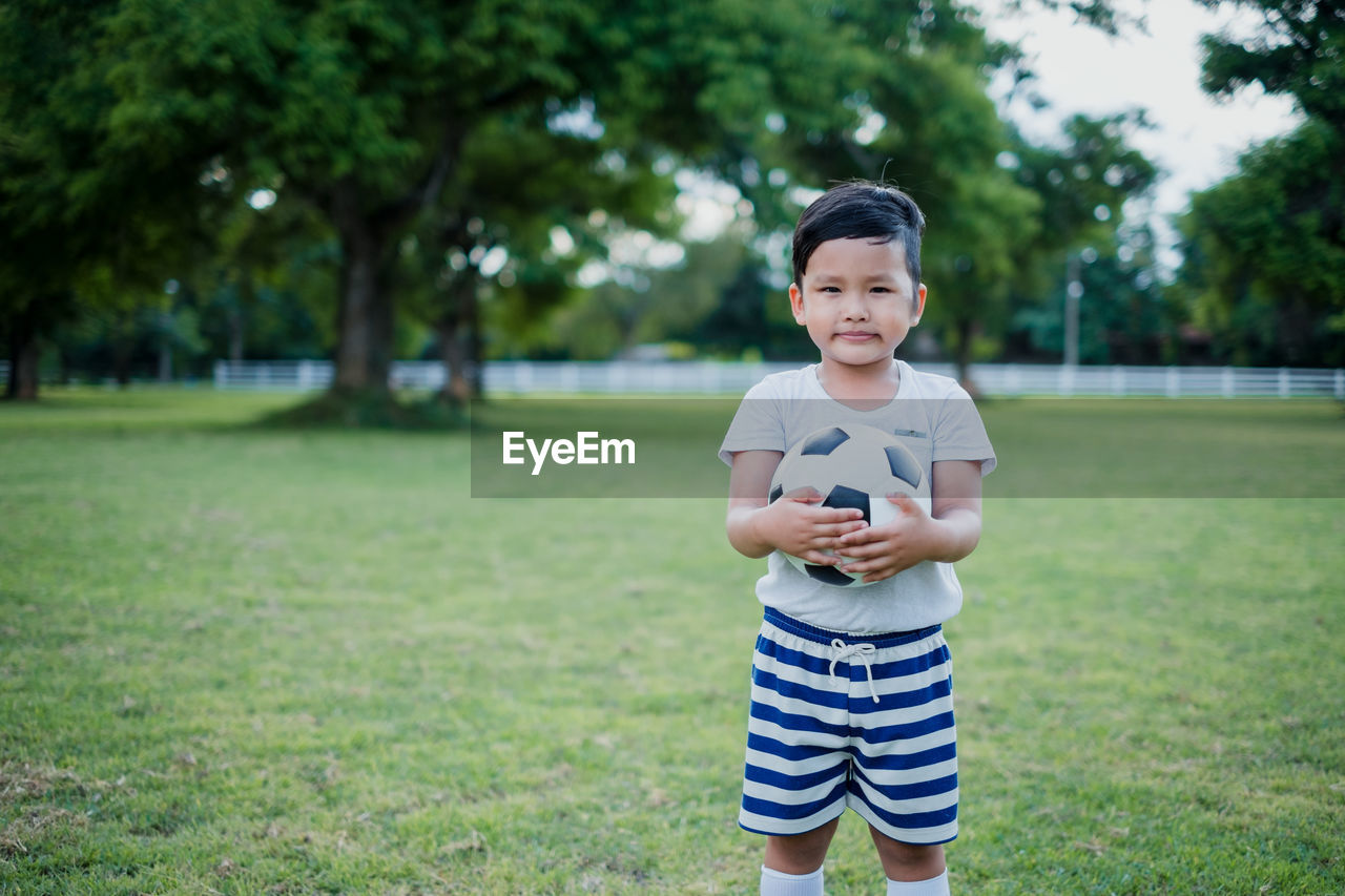 childhood, child, one person, plant, grass, real people, leisure activity, tree, casual clothing, lifestyles, focus on foreground, field, standing, looking at camera, boys, portrait, sport, front view, males, innocence