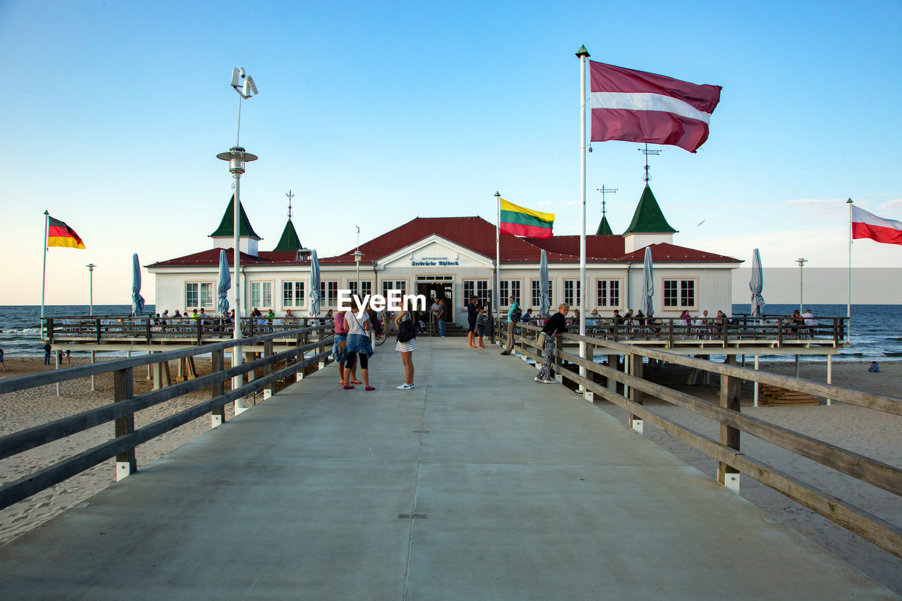 flag, sky, real people, architecture, built structure, water, building exterior, lifestyles, nature, people, men, women, group of people, patriotism, clear sky, day, railing, incidental people, outdoors