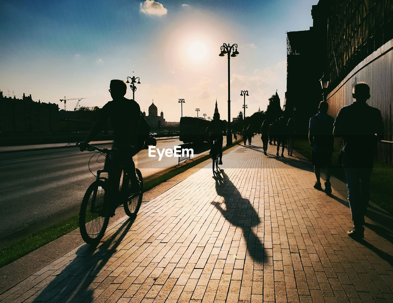 city, street, bicycle, sky, transportation, sunset, real people, sunlight, men, group of people, silhouette, shadow, lifestyles, nature, people, road, domestic, pets, footpath, architecture, riding, outdoors, sun