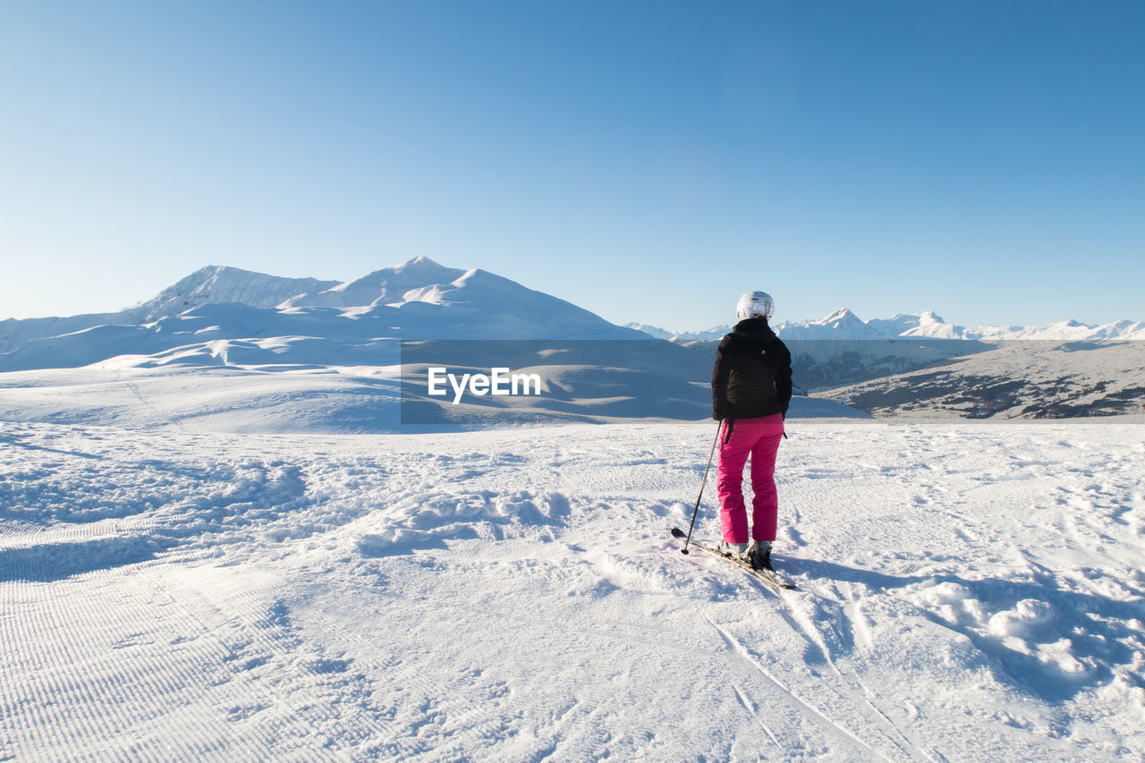 winter, mountain, cold temperature, snow, real people, rear view, sky, beauty in nature, full length, leisure activity, one person, scenics - nature, nature, lifestyles, sunlight, holiday, clothing, day, mountain range, warm clothing, snowcapped mountain