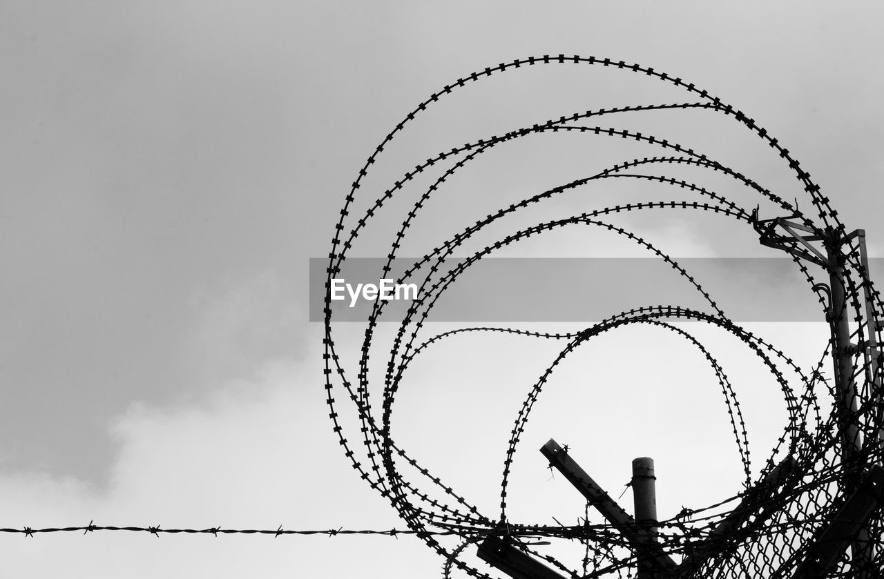 sky, low angle view, razor wire, nature, cloud - sky, no people, metal, sharp, protection, security, day, safety, spiral, outdoors, barbed wire, fence, arts culture and entertainment, architecture, built structure, amusement park