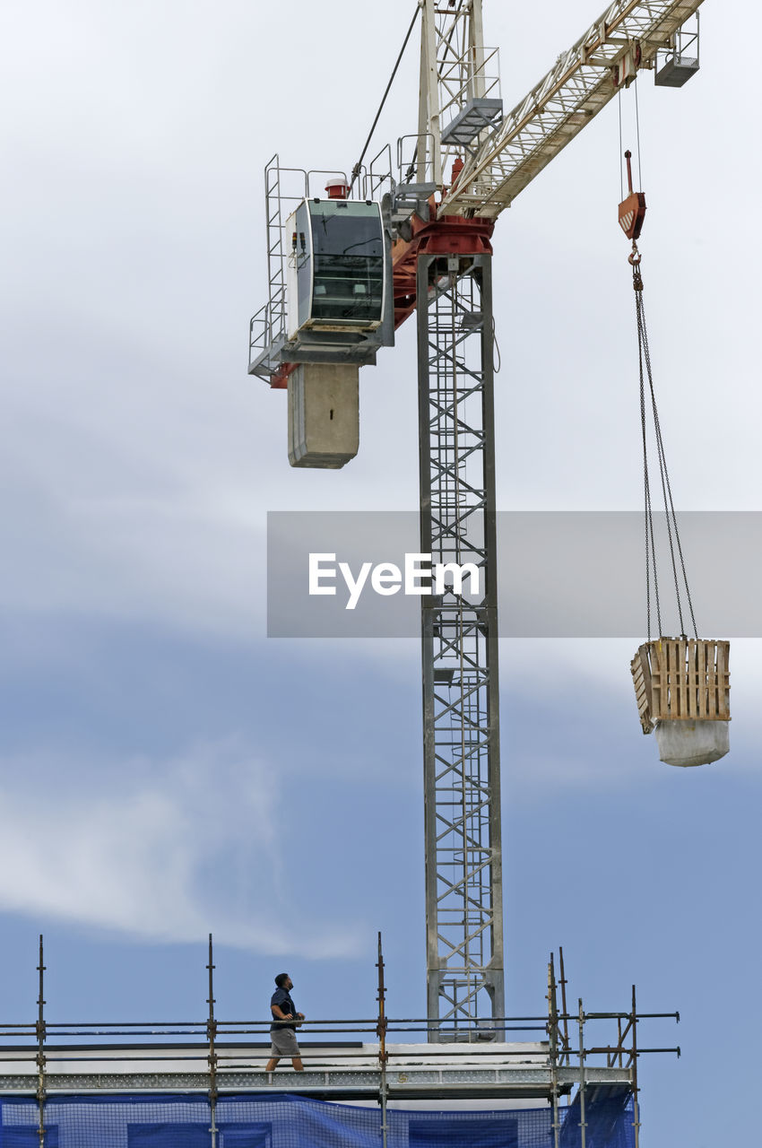 sky, machinery, crane - construction machinery, cloud - sky, construction industry, nature, construction site, development, low angle view, architecture, industry, day, built structure, outdoors, occupation, working, water, real people, metal, construction equipment