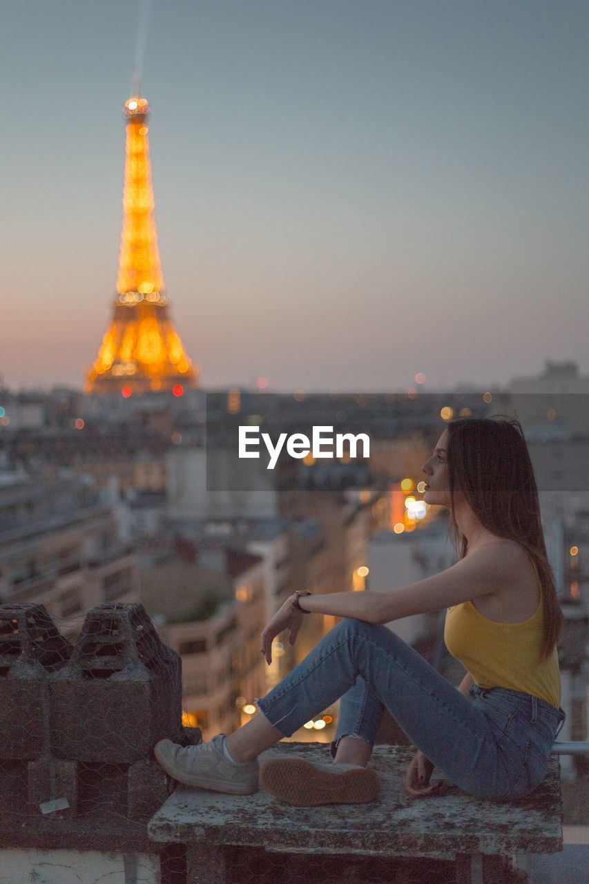 built structure, sky, architecture, building exterior, city, sunset, one person, nature, real people, travel destinations, casual clothing, tower, sitting, leisure activity, lifestyles, building, young adult, history, outdoors, cityscape, hairstyle, looking at view