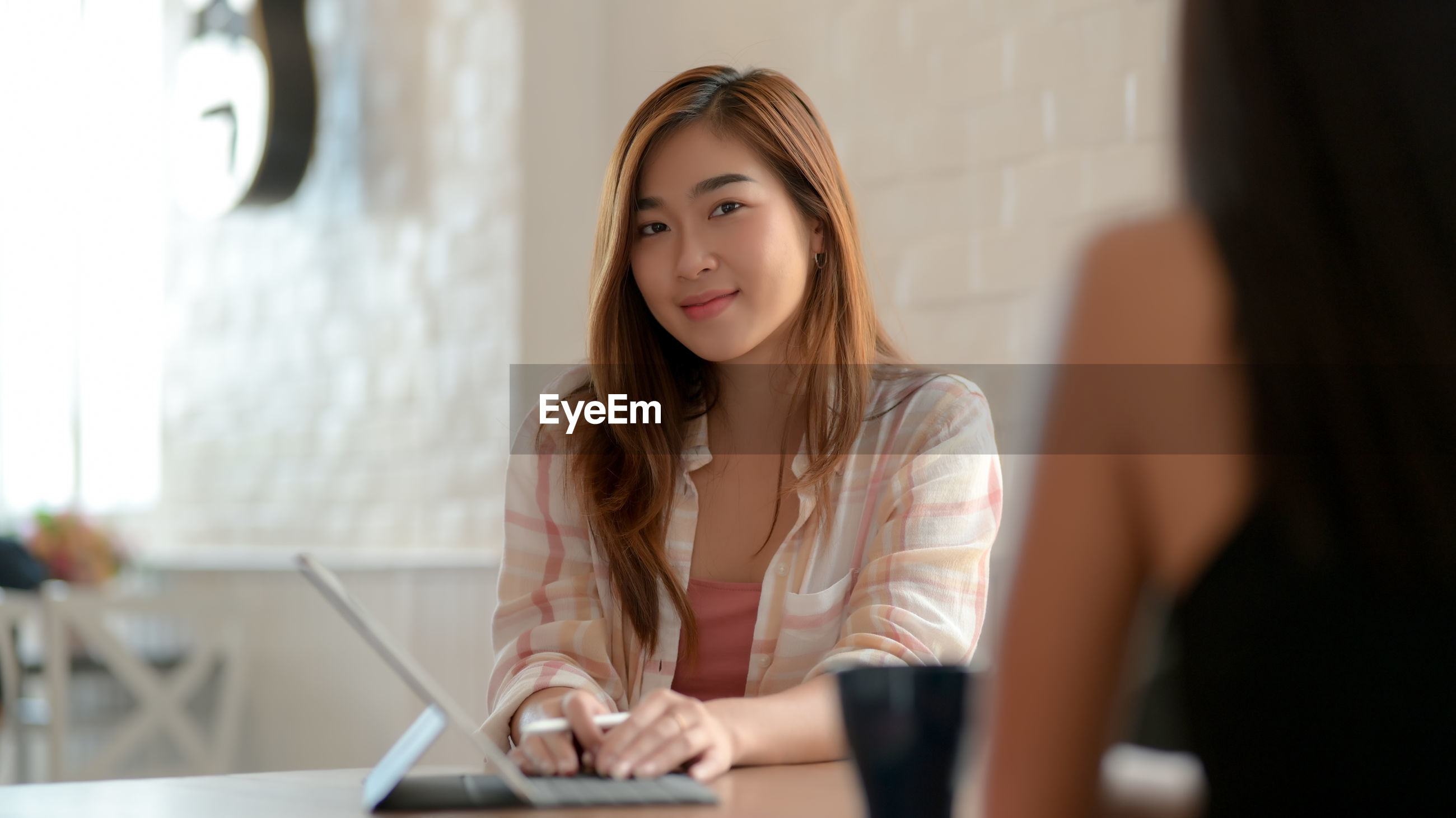 Smiling young woman using digital tablet at table