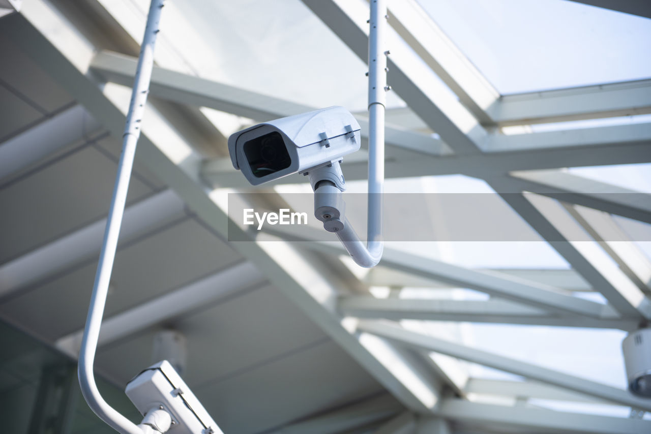 security camera, surveillance, technology, no people, focus on foreground, security, protection, safety, built structure, low angle view, security system, day, architecture, modern, control, close-up, photography themes, metal, connection, white color, ceiling, big brother - orwellian concept, electrical equipment