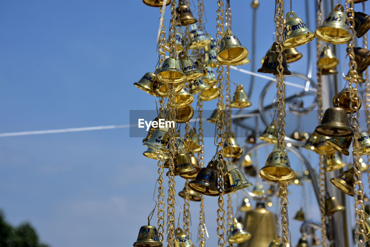 gold colored, sky, no people, metal, low angle view, hanging, focus on foreground, day, art and craft, blue, arts culture and entertainment, nature, religion, place of worship, outdoors, close-up, craft, music, decoration, belief, ornate