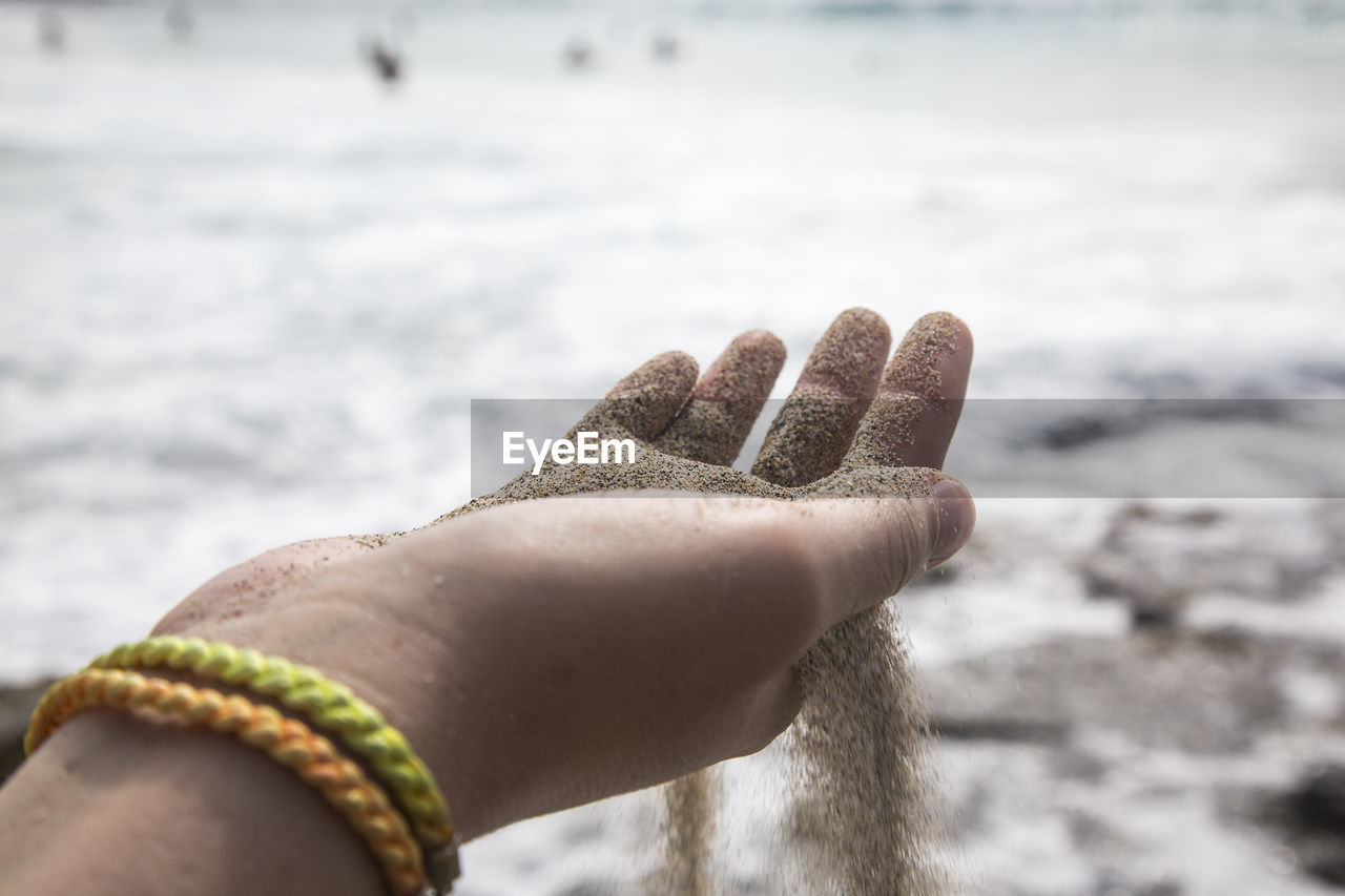 human hand, human body part, hand, one person, body part, focus on foreground, day, lifestyles, real people, close-up, human finger, personal perspective, leisure activity, finger, nature, water, unrecognizable person, bracelet, outdoors, human limb