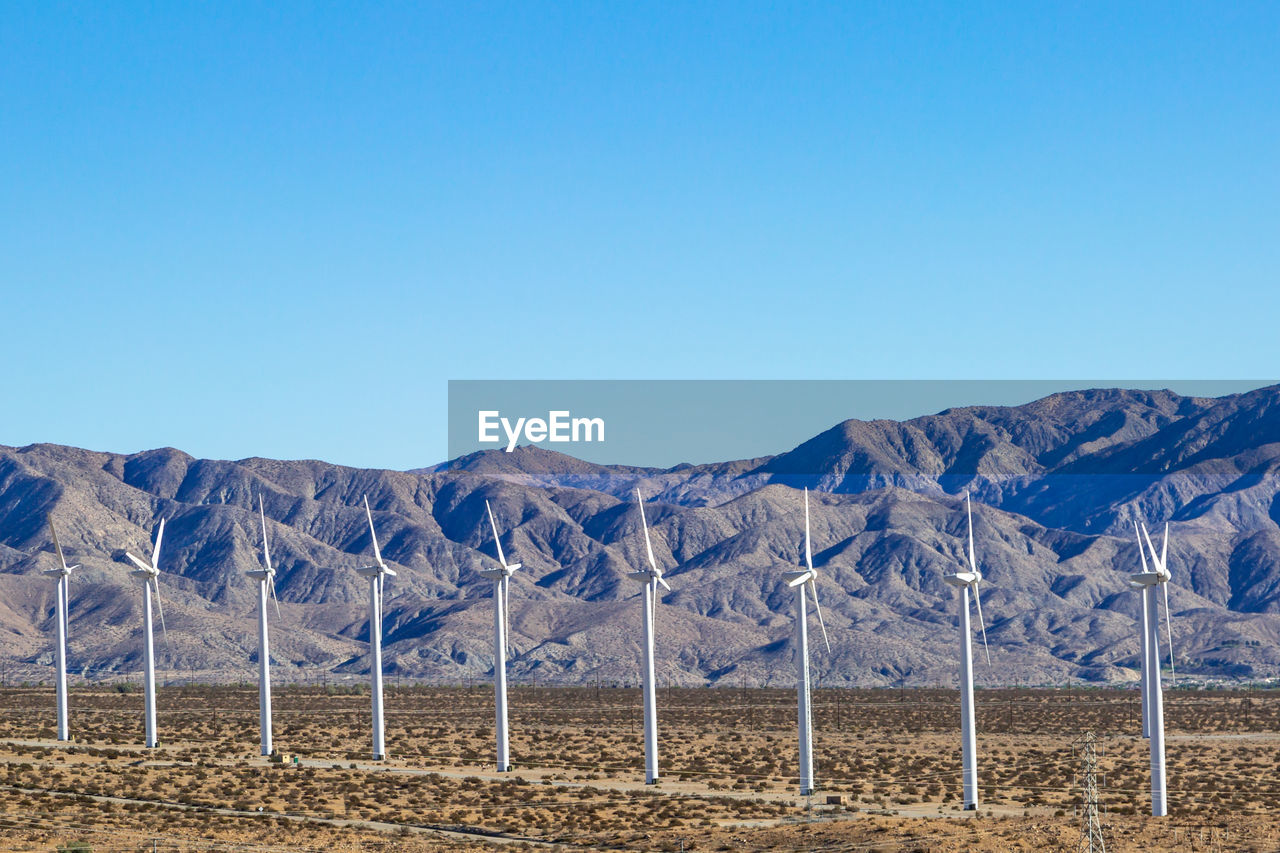 Scenic View Of Windmills On Field Against Clear Blue Sky
