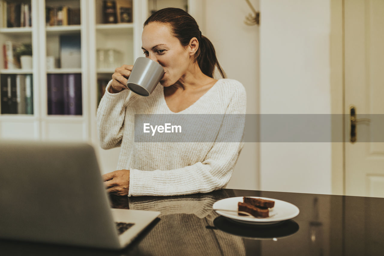 MID ADULT WOMAN USING LAPTOP ON TABLE AT HOME