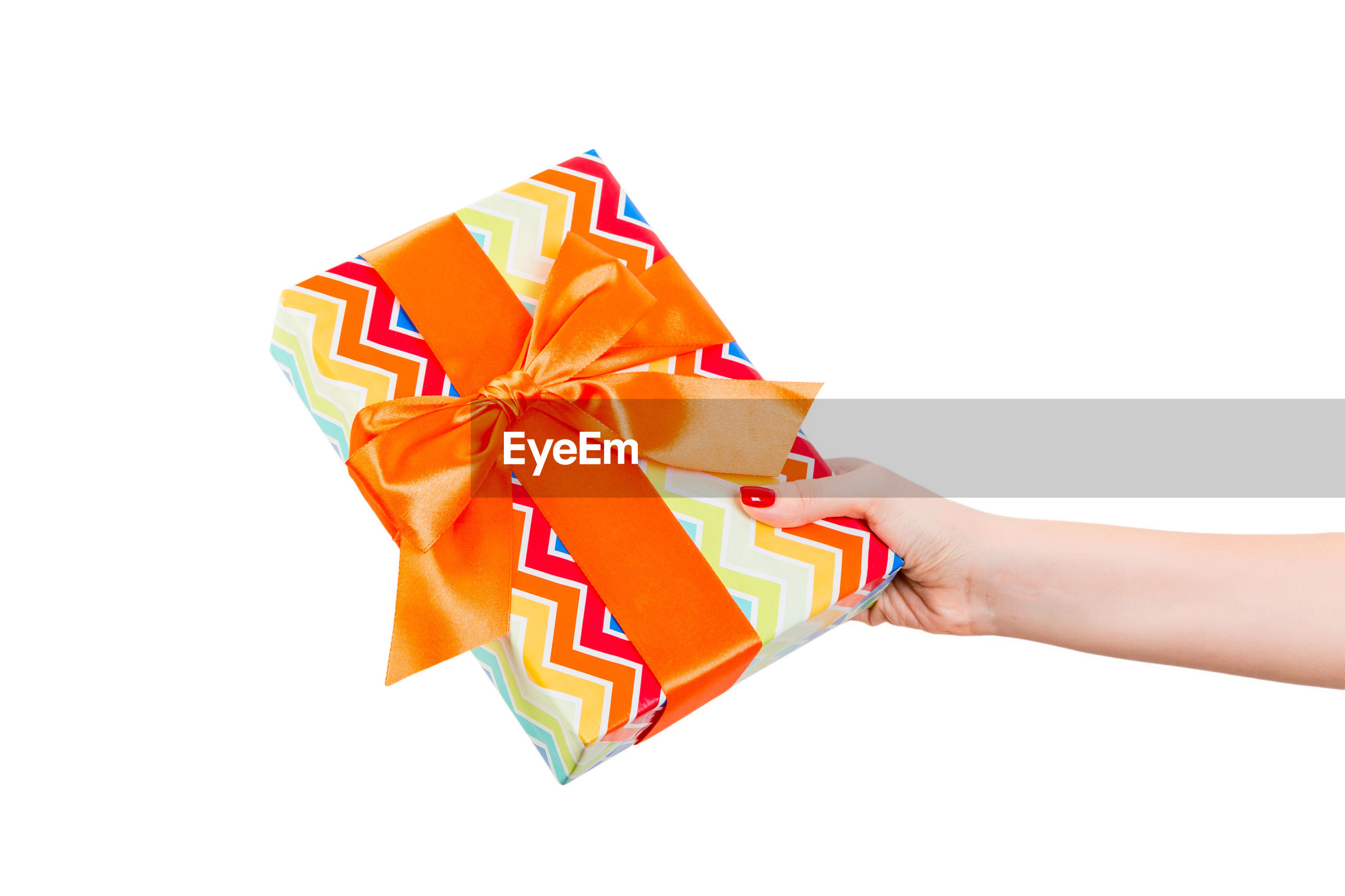 Cropped hand holding gift against white background