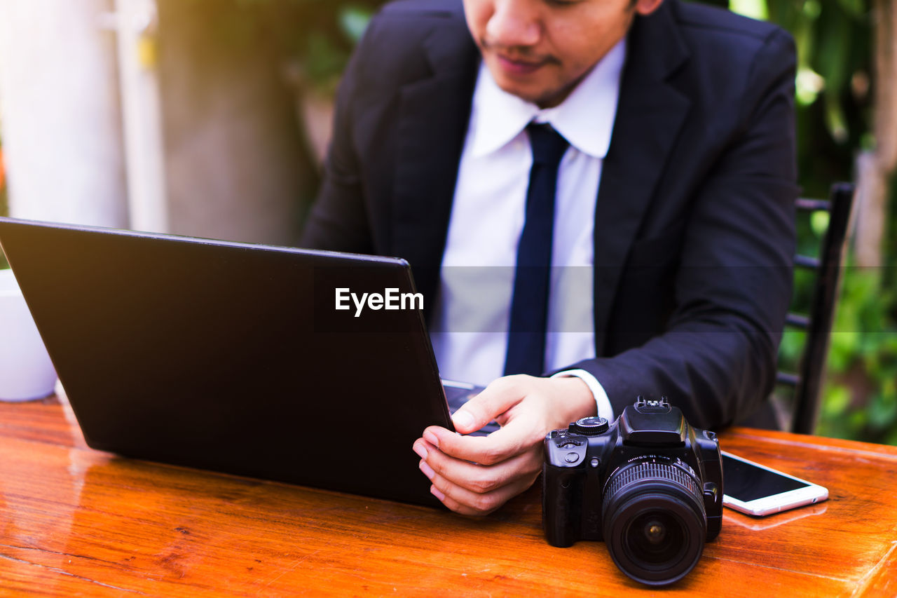 Midsection of businessman using laptop by camera and mobile phone on table