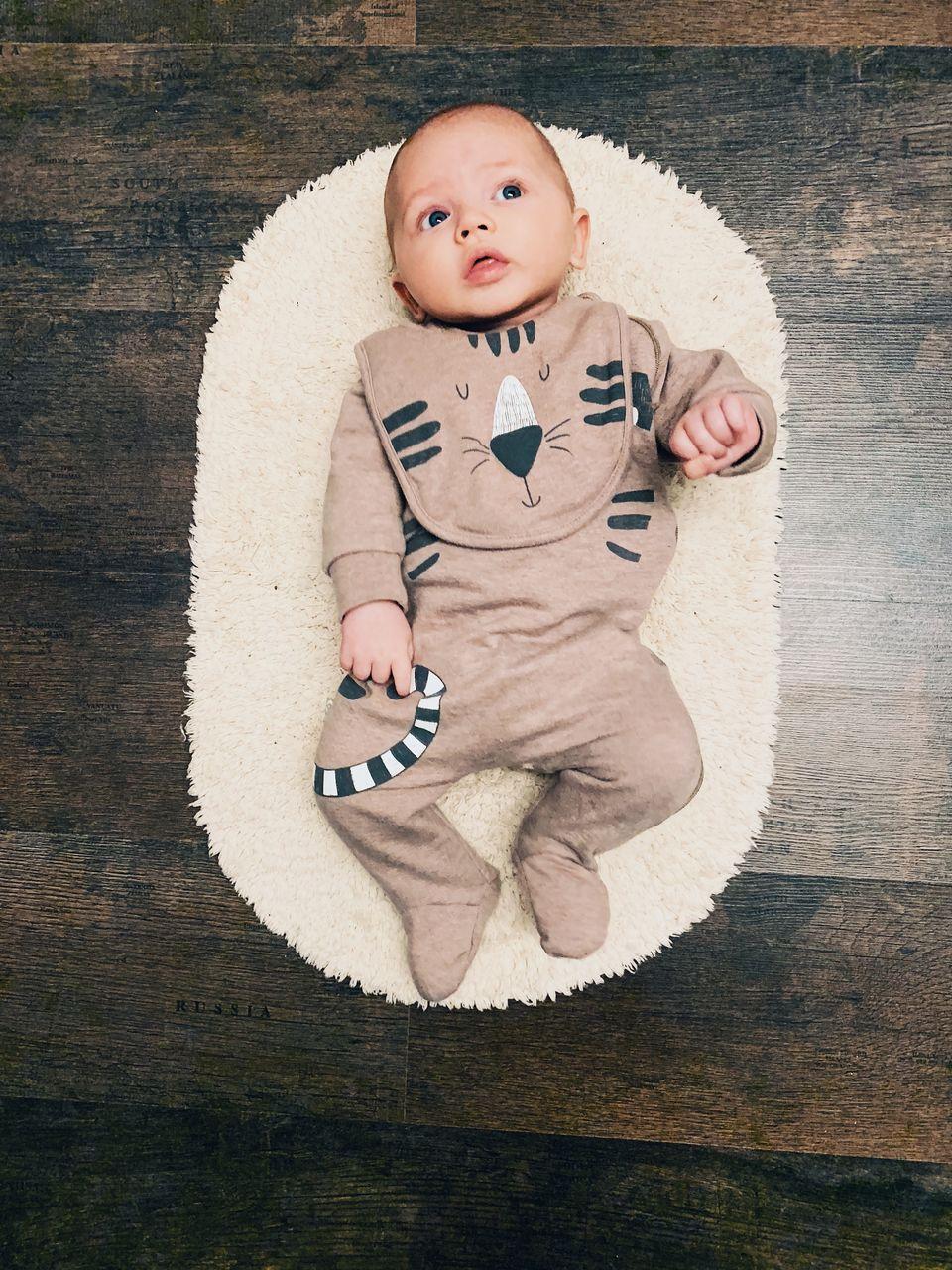 High angle view of cute baby boy lying on rug