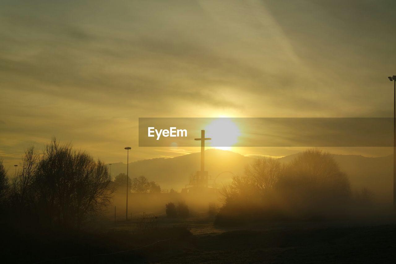 Silhouette cross on field during sunrise