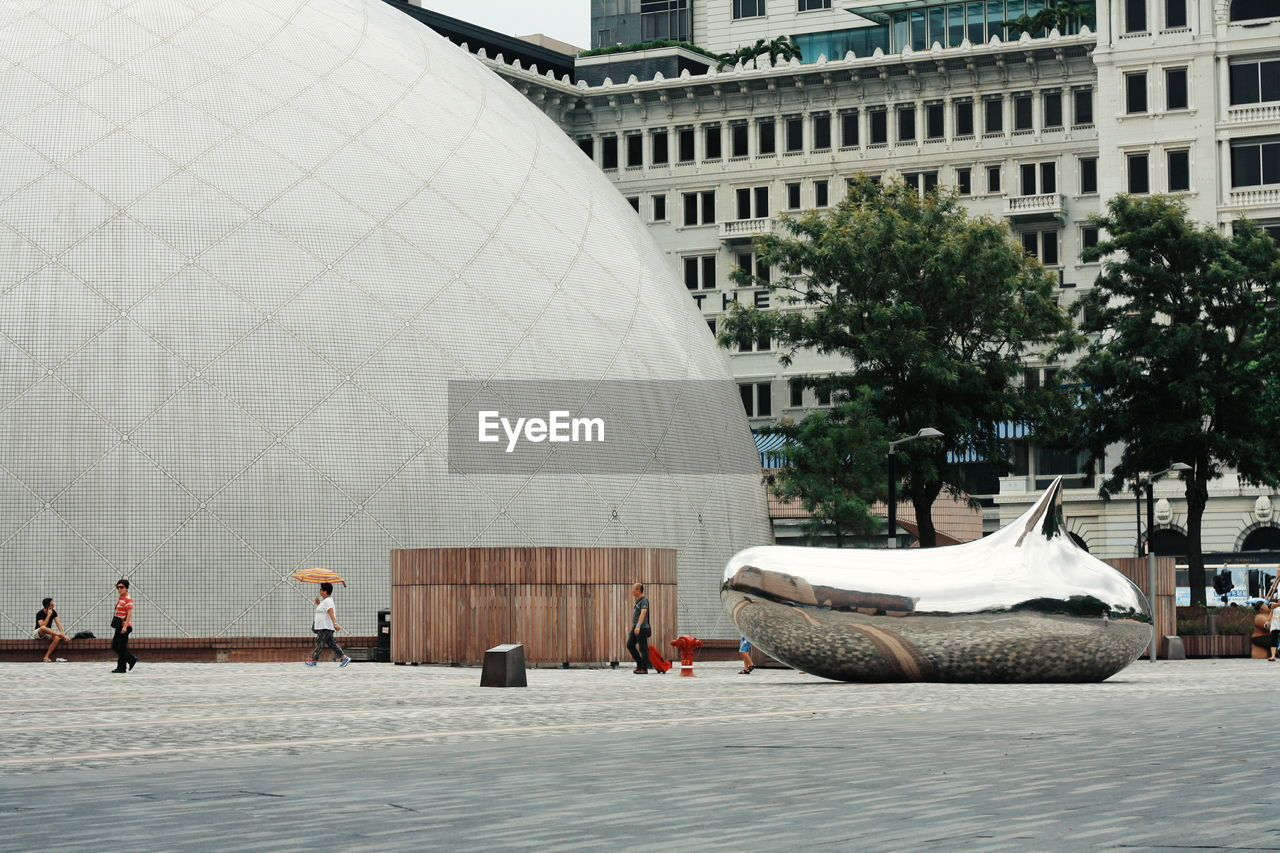 Modern building of sphere shape with sculpture of drop on town square