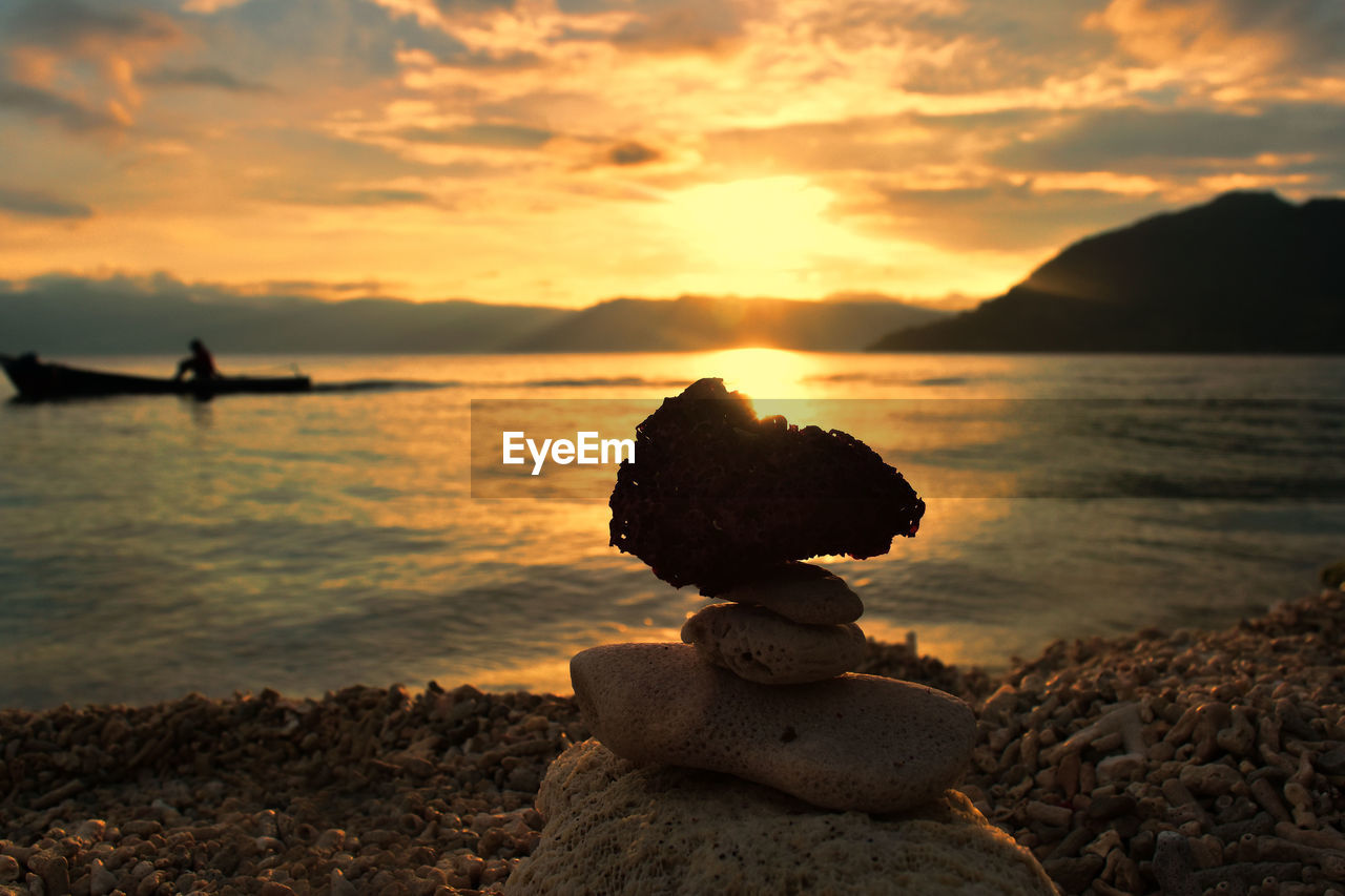 sunset, sky, rock, solid, rock - object, water, beauty in nature, cloud - sky, scenics - nature, sea, beach, tranquil scene, tranquility, land, orange color, nature, stone - object, no people, stack, outdoors, pebble