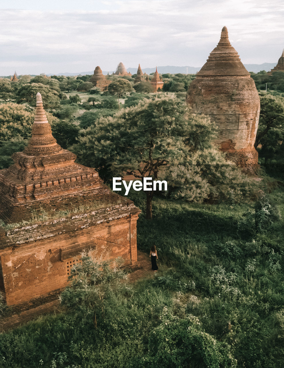 Ancient temple amidst tress against sky