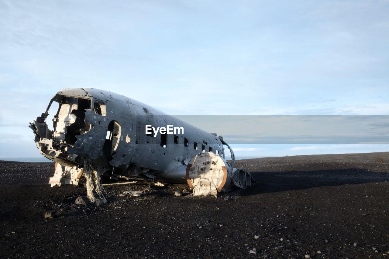 Damaged airplane on beach against sky