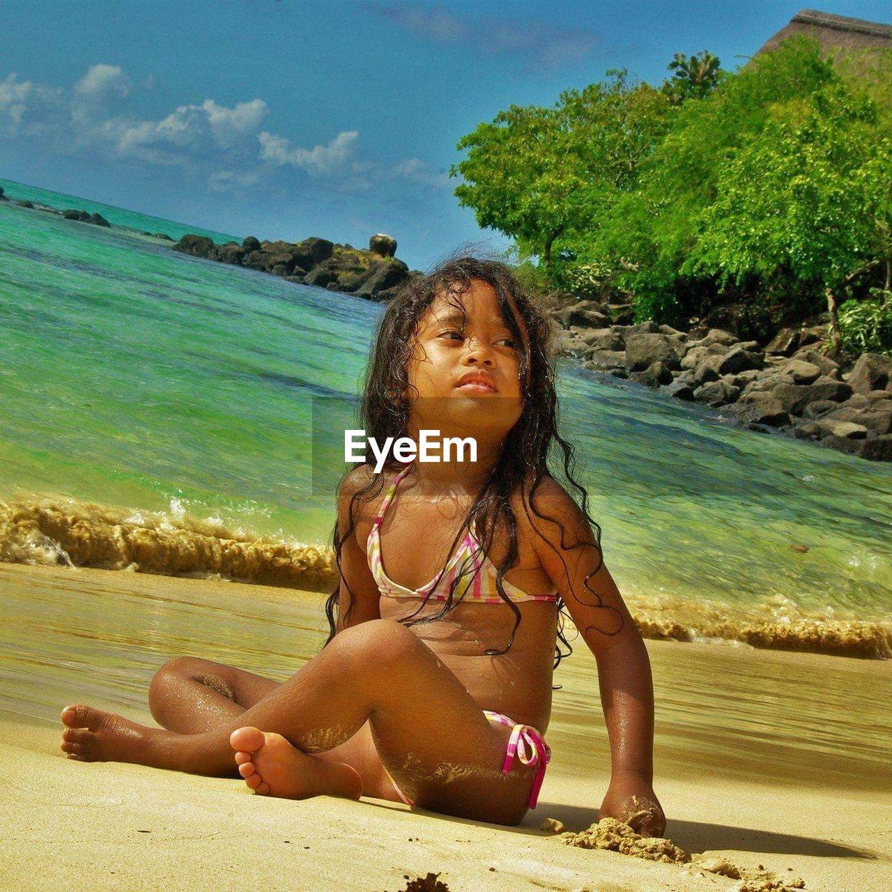Girl in bikini sitting on shore at beach during sunny day