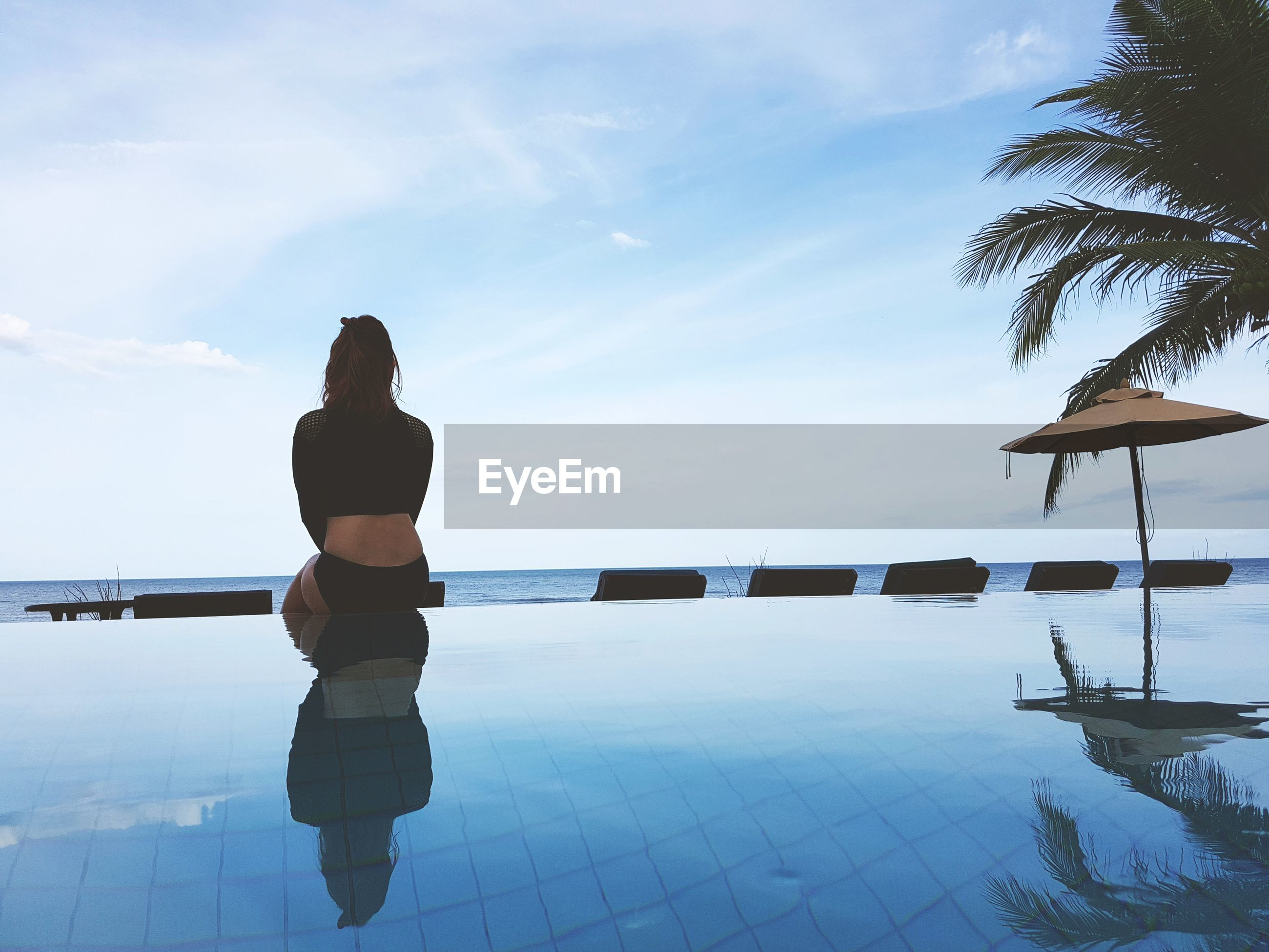 Rear view of thoughtful woman sitting by swimming pool against sky