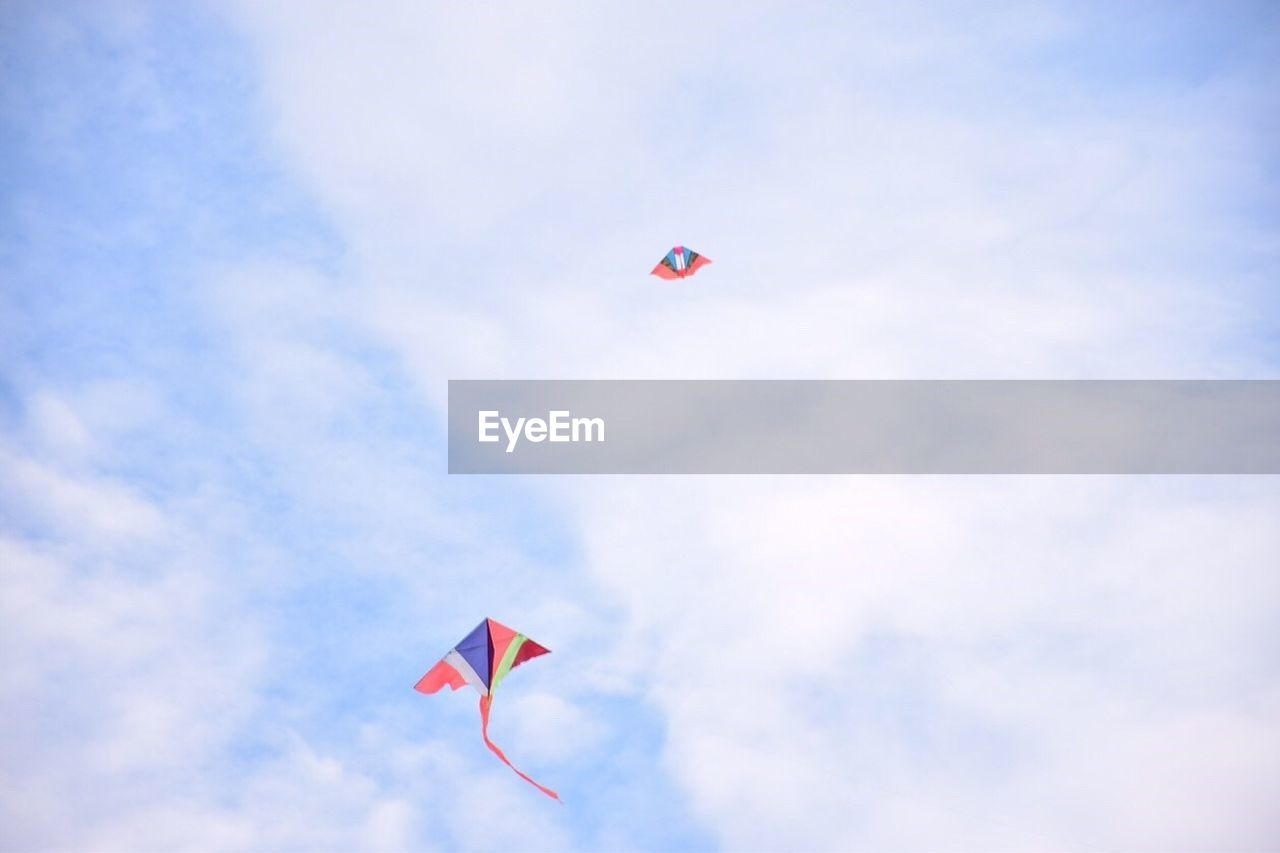 sky, flying, cloud - sky, red, low angle view, nature, day, mid-air, kite, kite - toy, freedom, no people, outdoors, environment, tranquility, flag, wind, blue, leisure activity