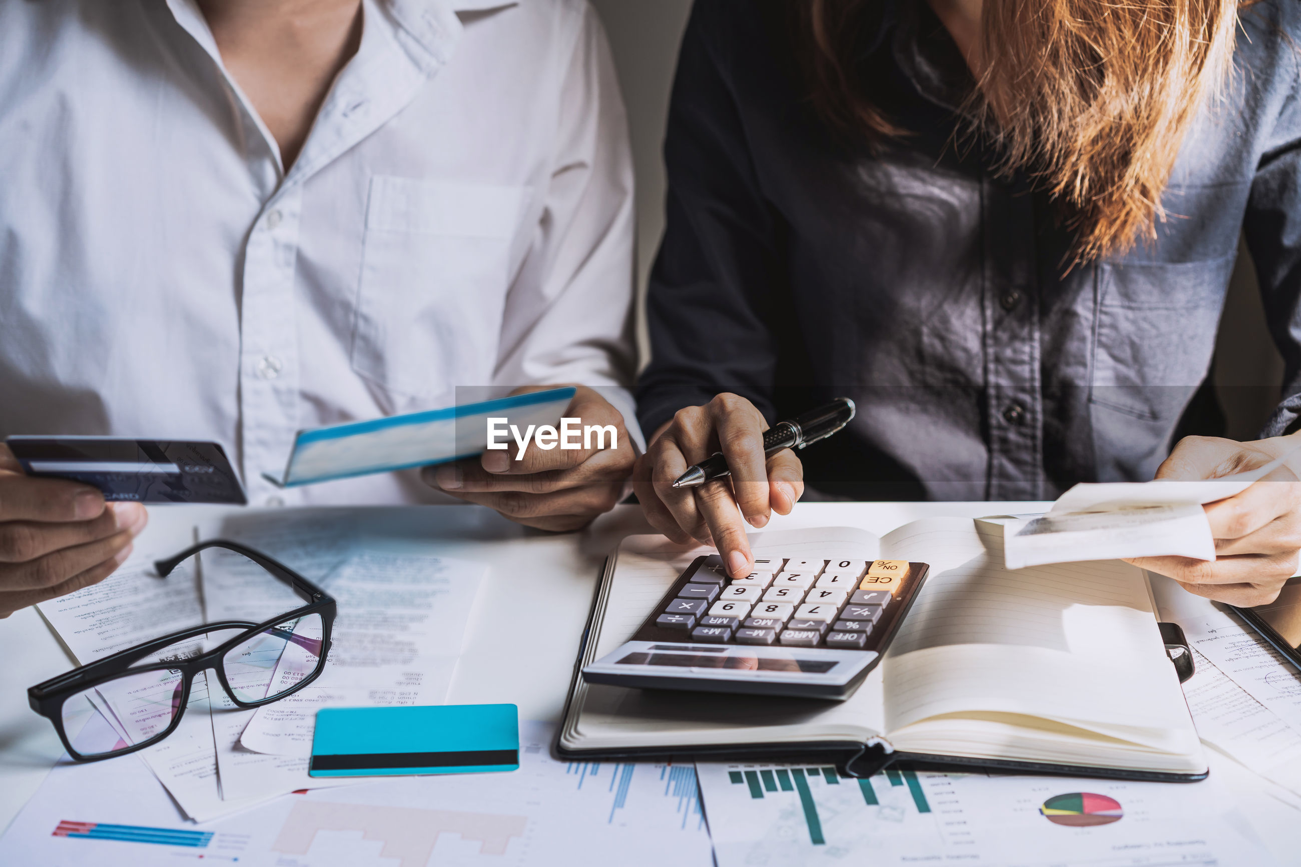Midsection of female colleagues analyzing financial bills