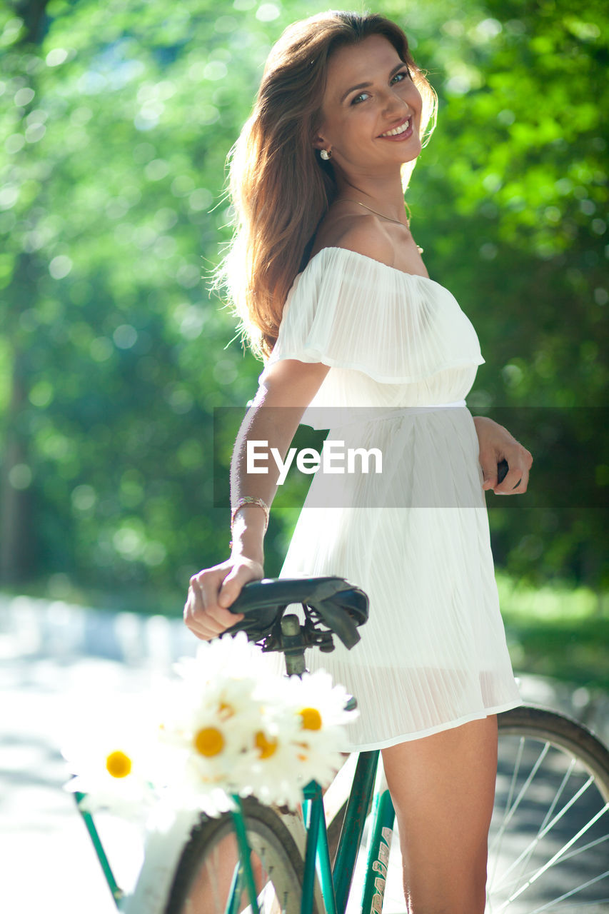 women, real people, one person, lifestyles, leisure activity, bicycle, transportation, casual clothing, young women, adult, young adult, beautiful woman, smiling, hairstyle, three quarter length, day, beauty, land vehicle, hair, fashion, outdoors, riding
