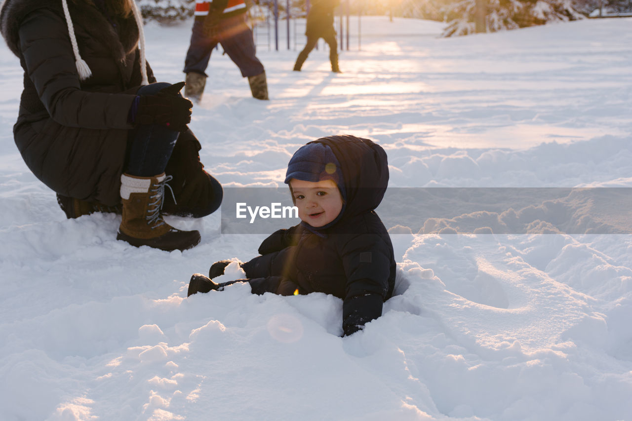Full Length Portrait Of Happy Baby Boy Sitting On Snow Covered Landscape