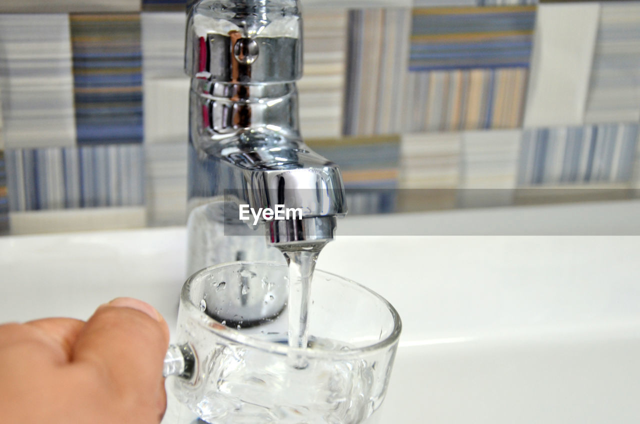 Cropped Image Of Person Filling Water In Glass