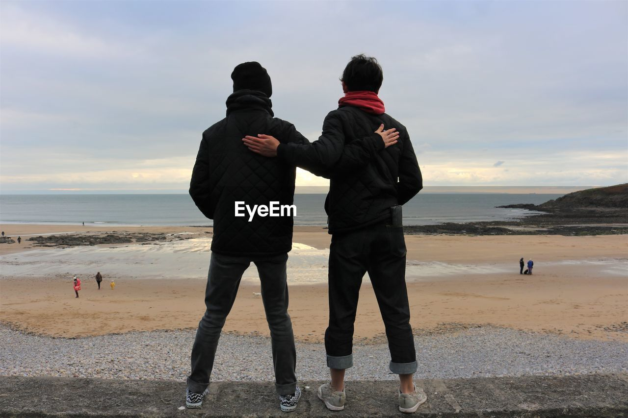 Rear view of friends standing at beach against sky