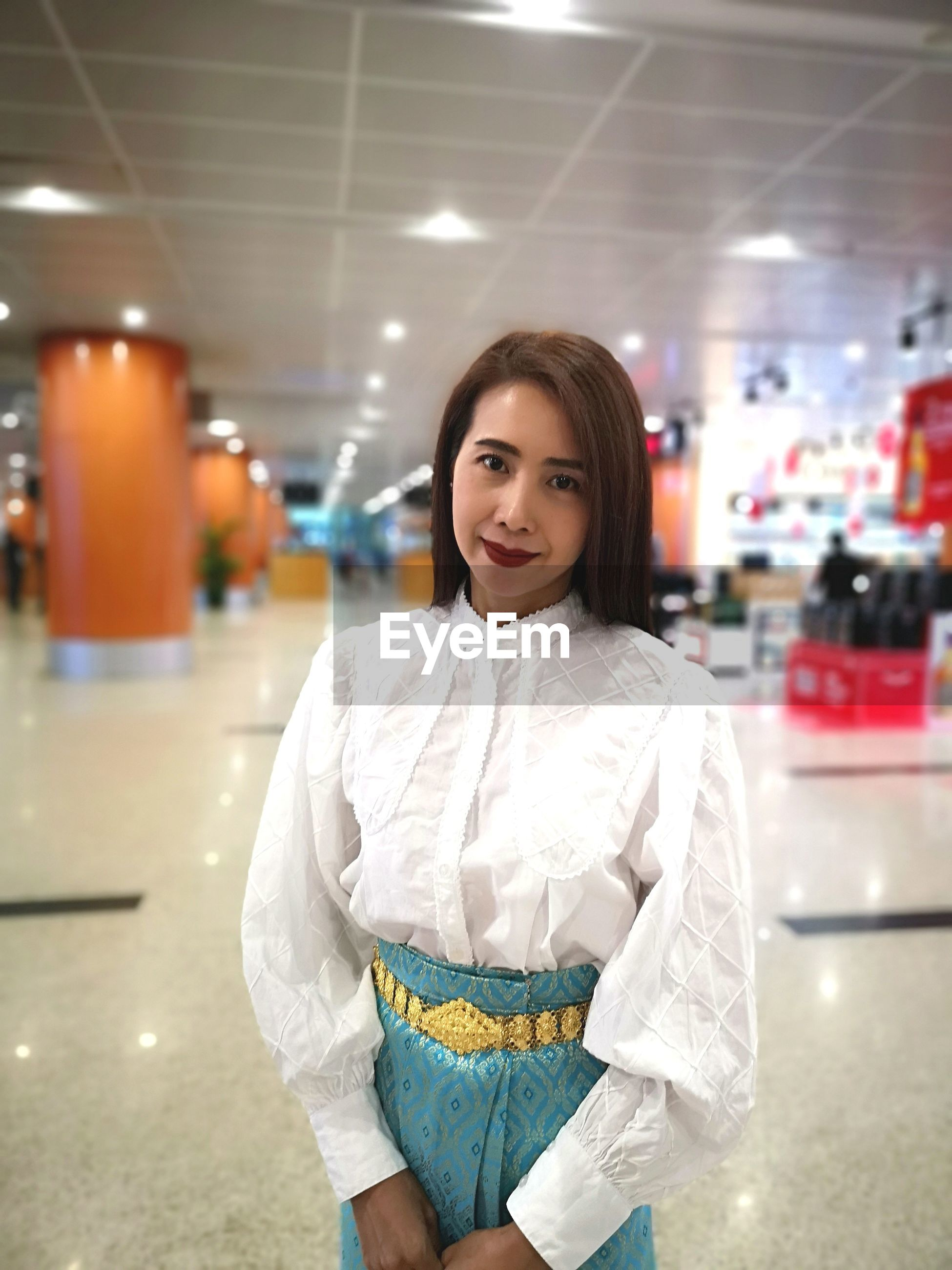 Portrait of smiling woman standing in shopping mall