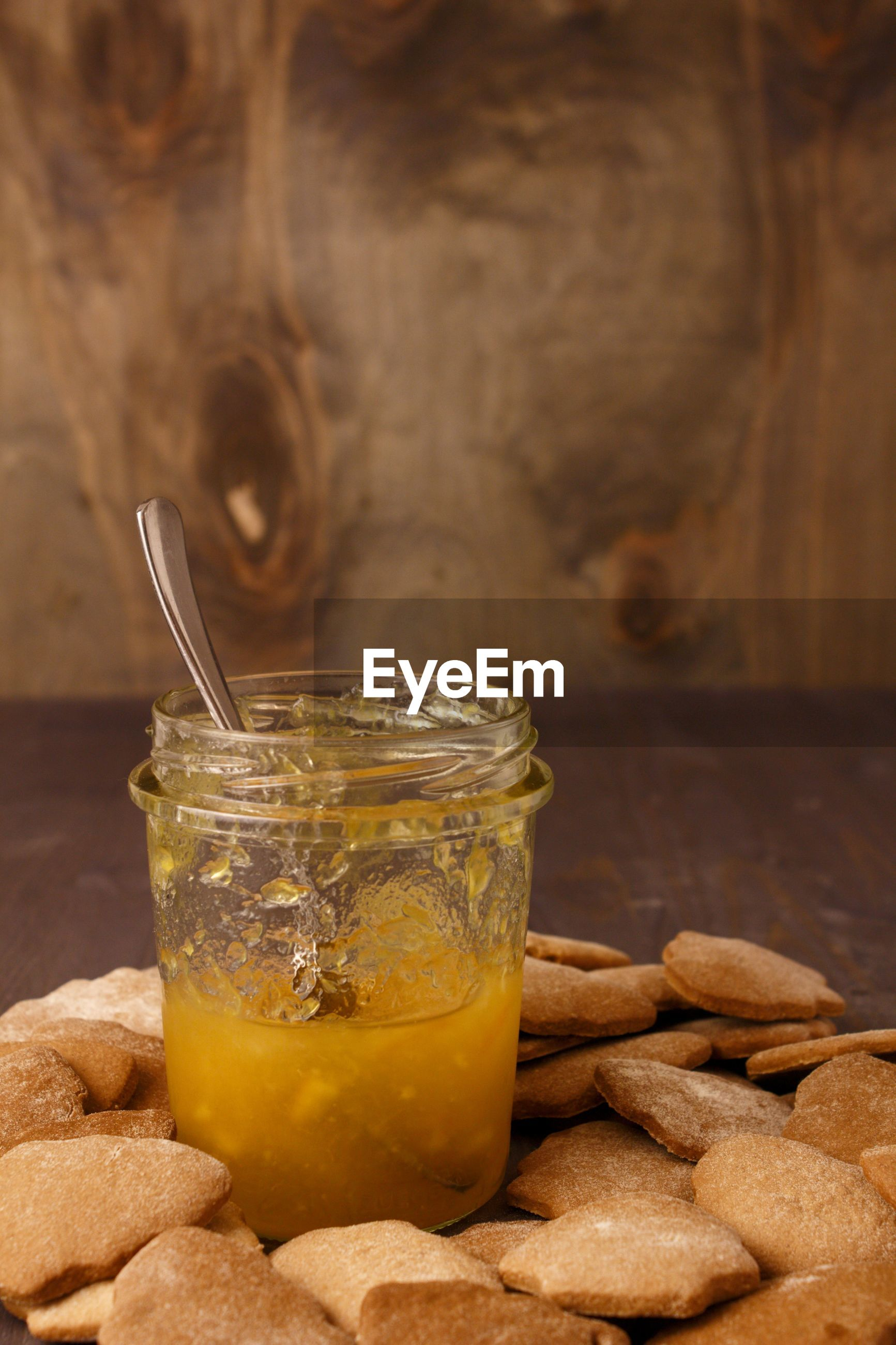 Orange jam in a glass jar with a spoon. on the table with ginger homemade cookies