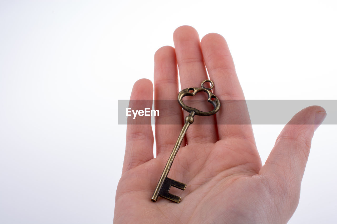 Cropped image of hand holding antique key against white background