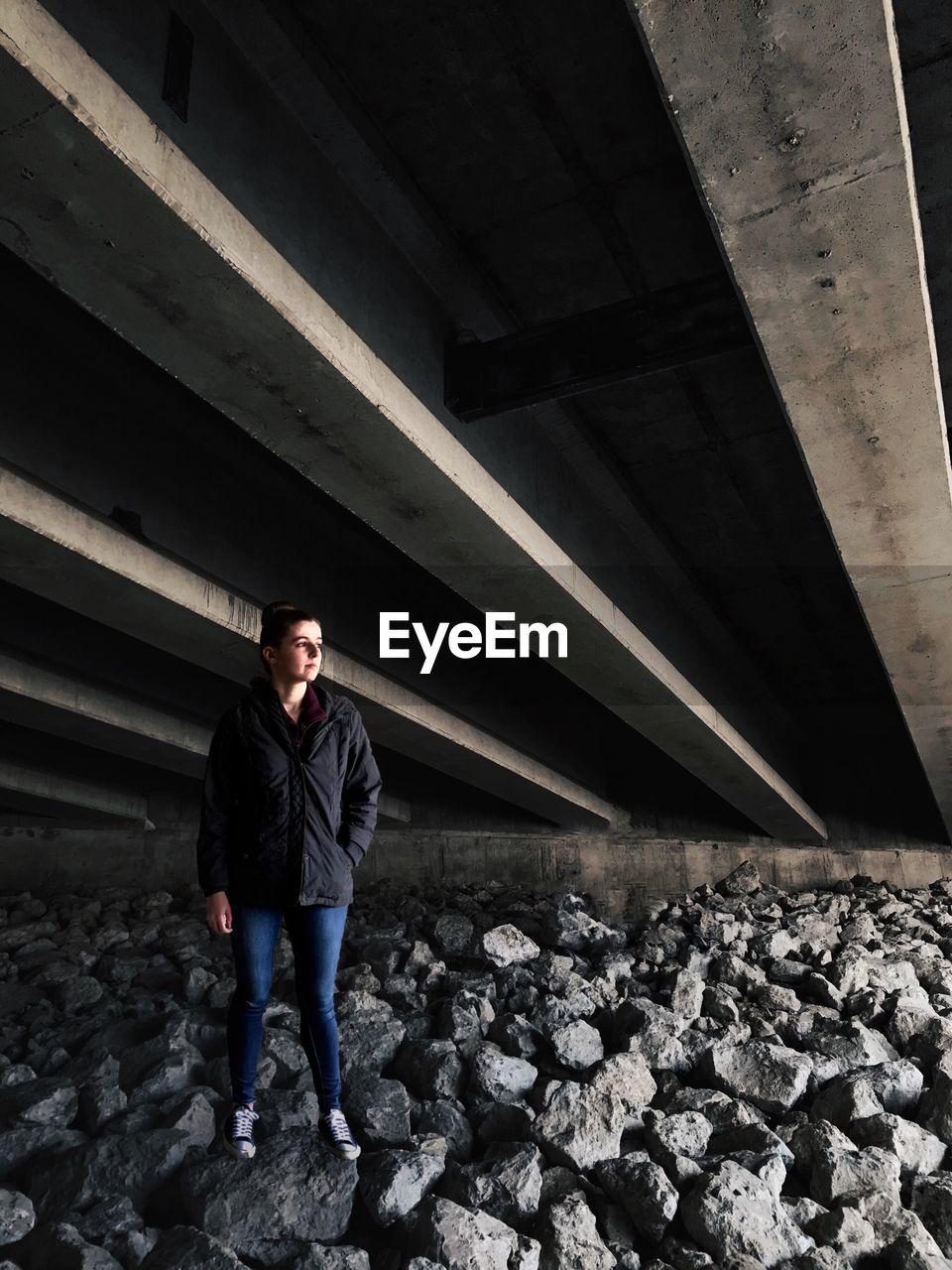 Full Length Of Woman Standing On Rocks Under Bridge