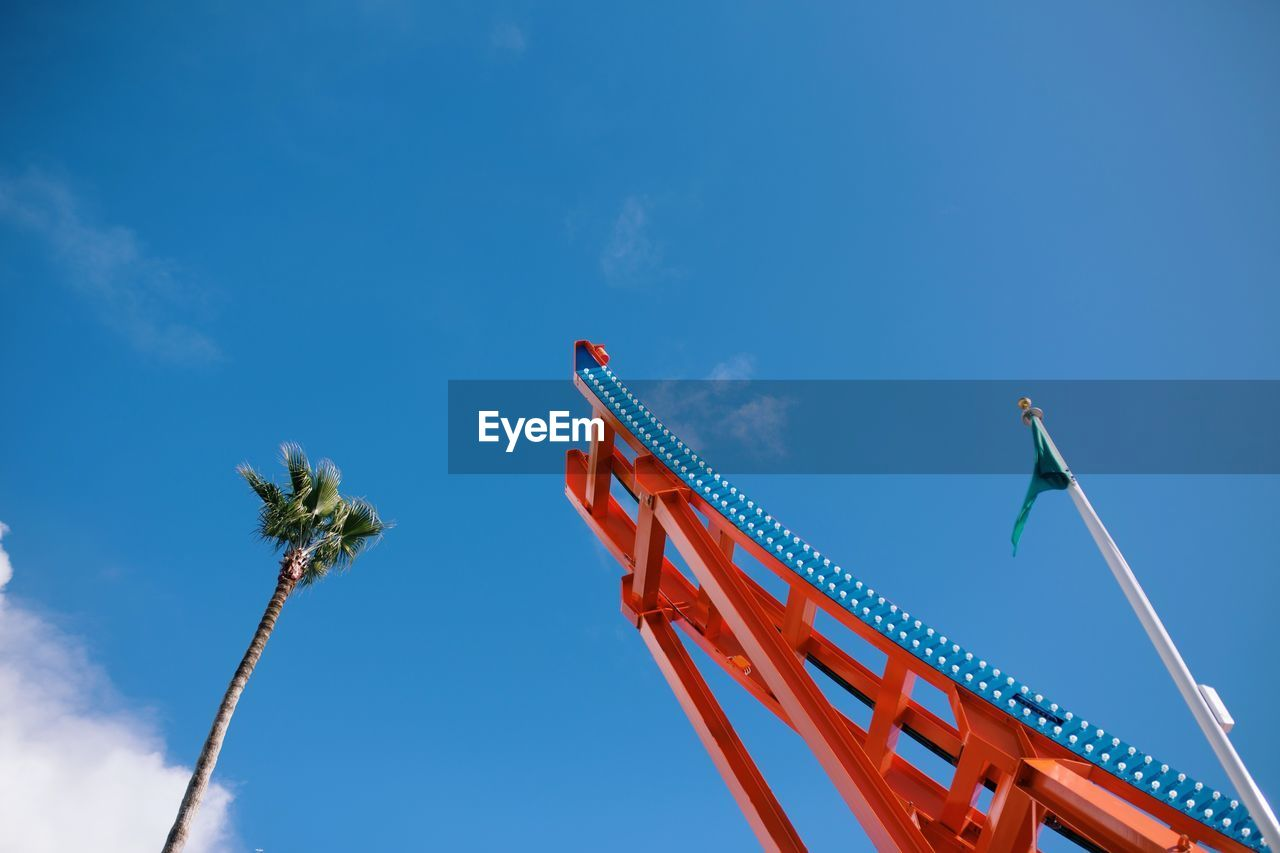 sky, low angle view, blue, nature, cloud - sky, no people, day, outdoors, arts culture and entertainment, palm tree, tropical climate, tall - high, red, plant, architecture, tree, machinery, built structure, amusement park, fun