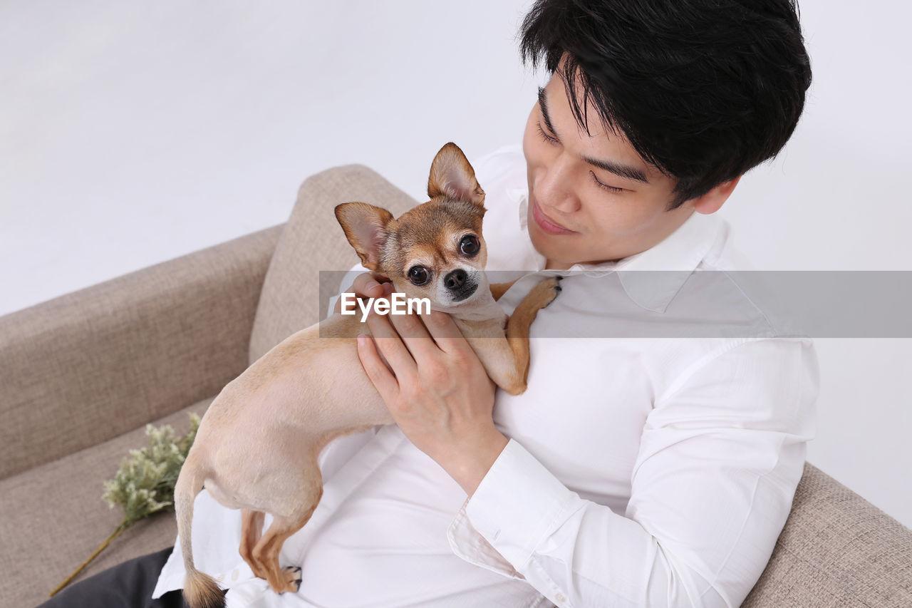 Man sitting with dog on sofa against white background