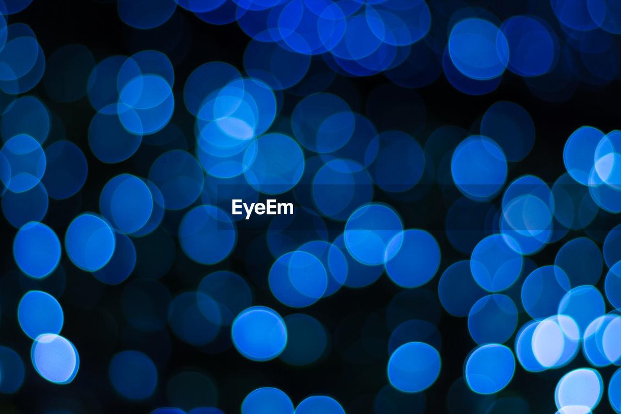 Defocused image of illuminated blue lights at night