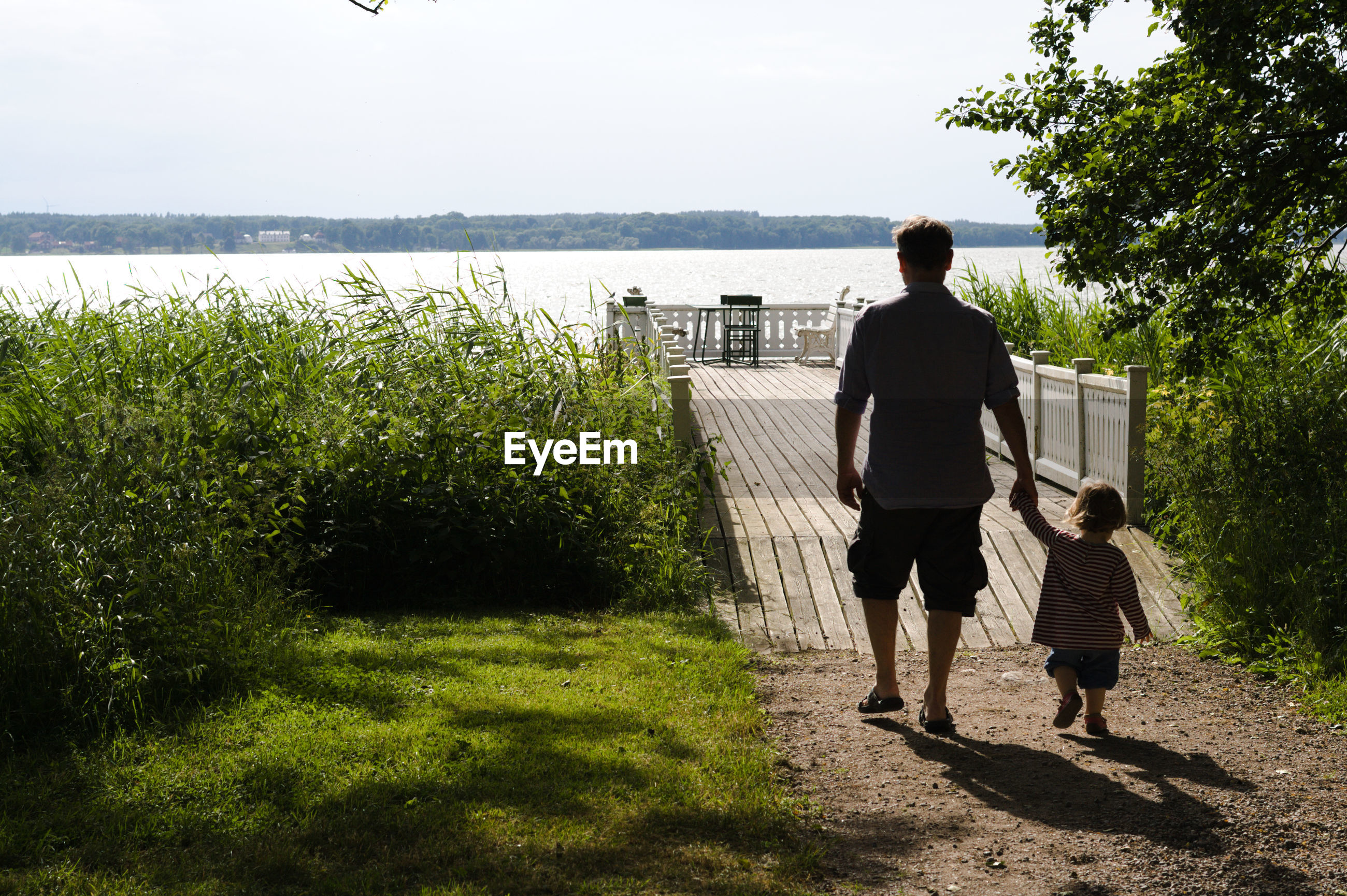 Father and daughter walking at lakeshore against sky